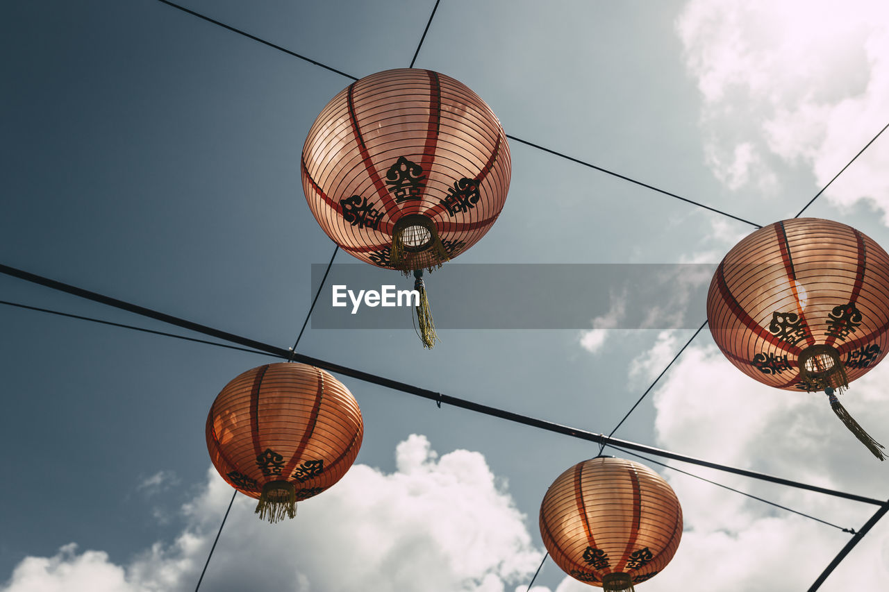 Low Angle View Of Chinese Lanterns Hanging On Cable Against Sky