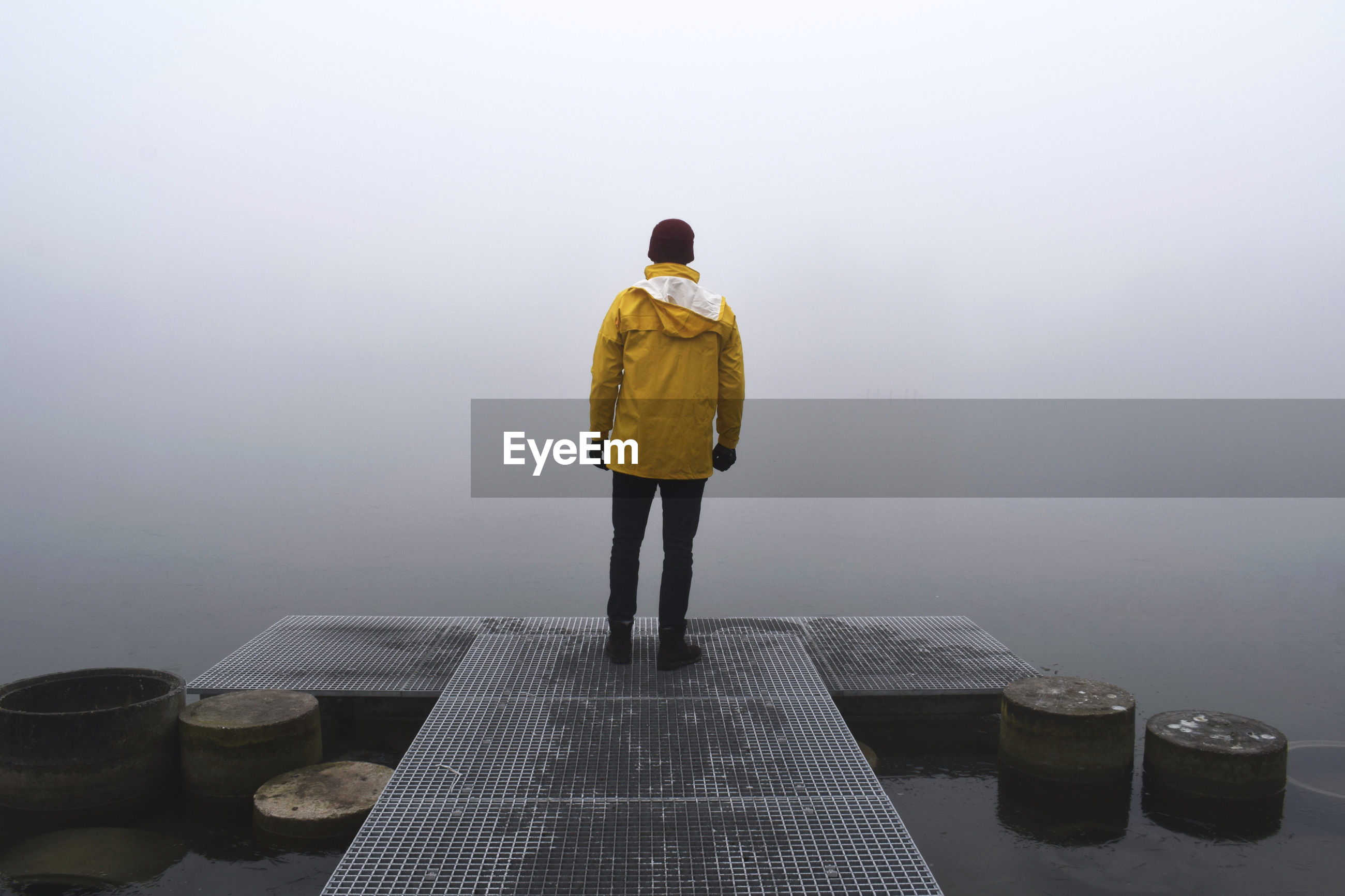 Rear view of man standing on jetty