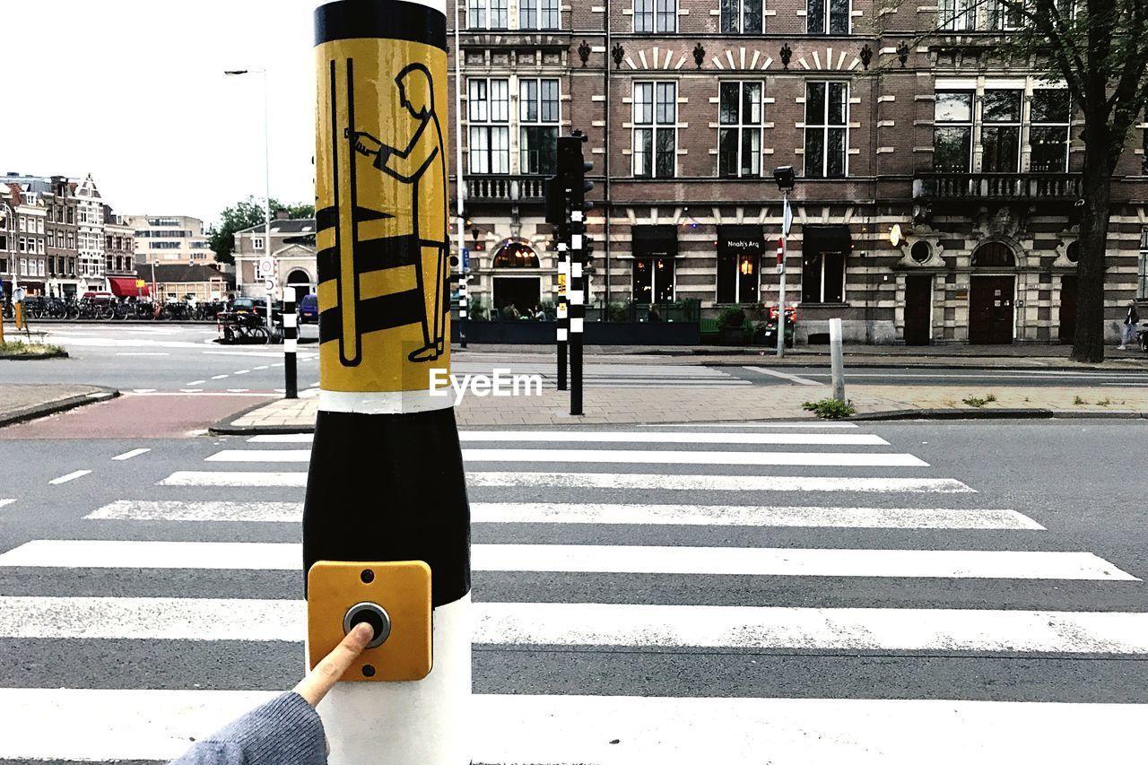 city, street, sign, transportation, road, road marking, symbol, architecture, marking, crosswalk, crossing, building exterior, zebra crossing, day, built structure, mode of transportation, yellow, road sign, city life, communication, city street, outdoors, guidance