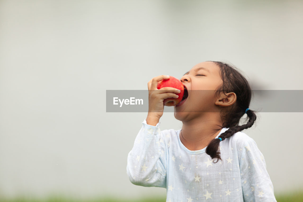 child, childhood, one person, front view, casual clothing, real people, girls, females, lifestyles, focus on foreground, holding, food and drink, innocence, women, leisure activity, mouth open, standing, mouth