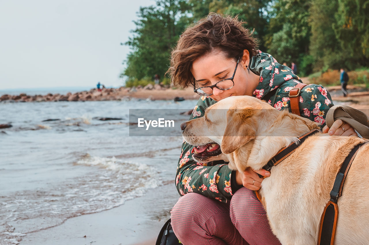 A girl kisses a dog on the head against the background of the sea. walk with a fawn labrador