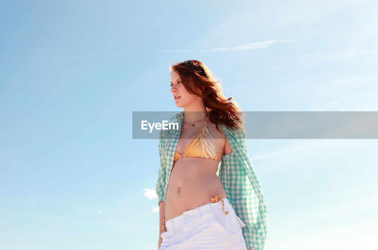 Low Angle View Of Sensuous Young Woman Standing Against Sky
