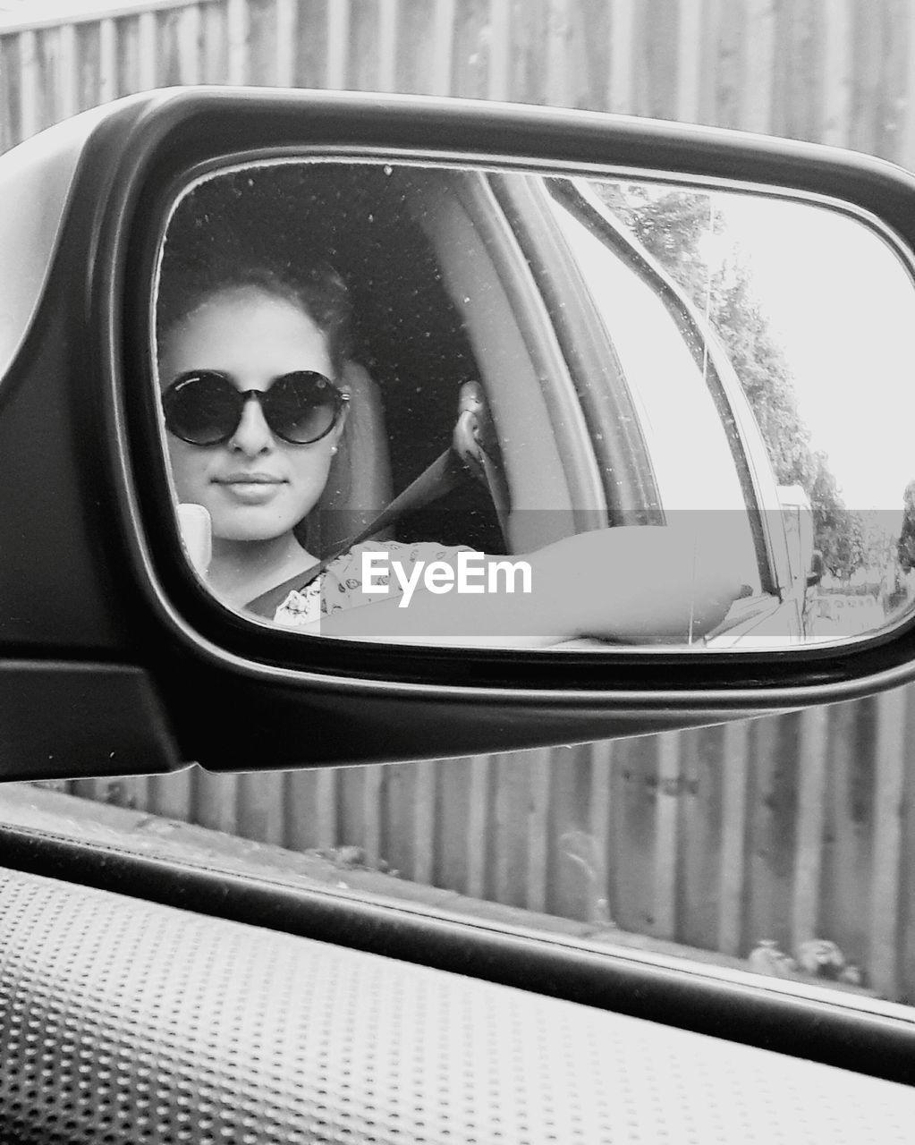 Portrait Of Young Woman Wearing Sunglasses Reflecting On Car Side-View Mirror