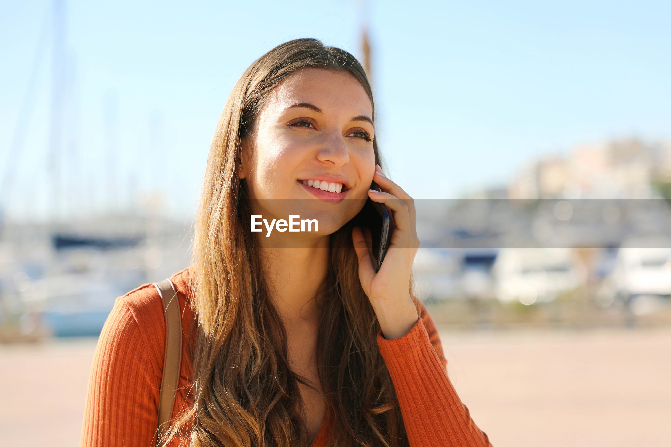 Close-up of thoughtful young woman talking on phone while standing in city