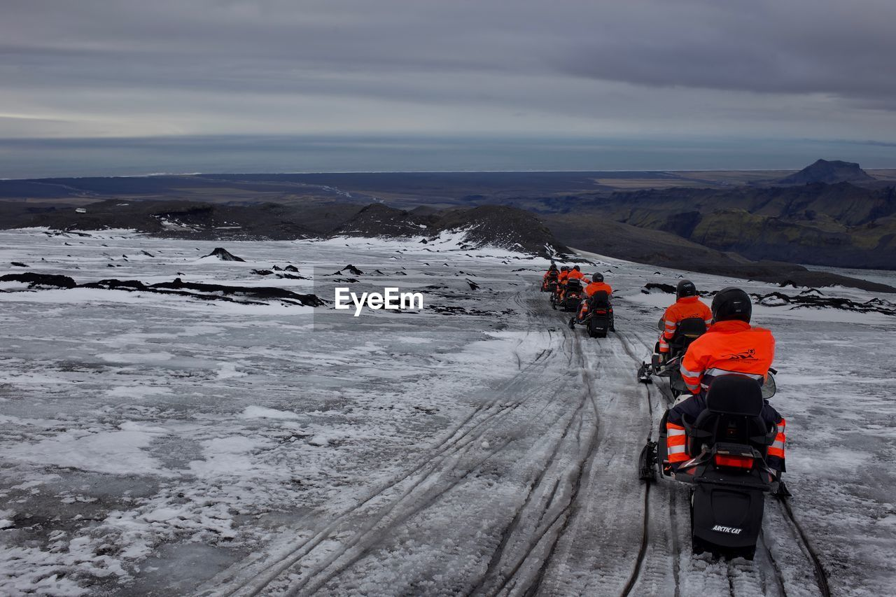 Rear View Of People Snowmobiling During Winter