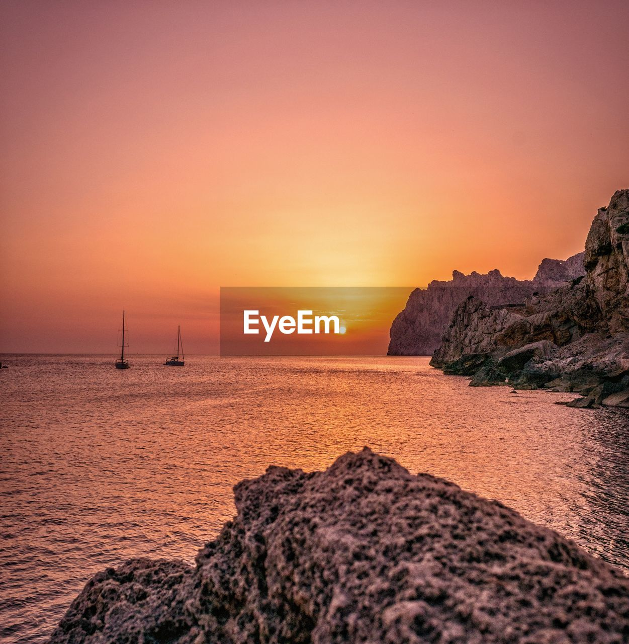 sunset, sea, sky, water, scenics - nature, beauty in nature, tranquility, rock, tranquil scene, orange color, idyllic, horizon over water, rock - object, solid, nature, horizon, no people, sun, land, outdoors, sailboat