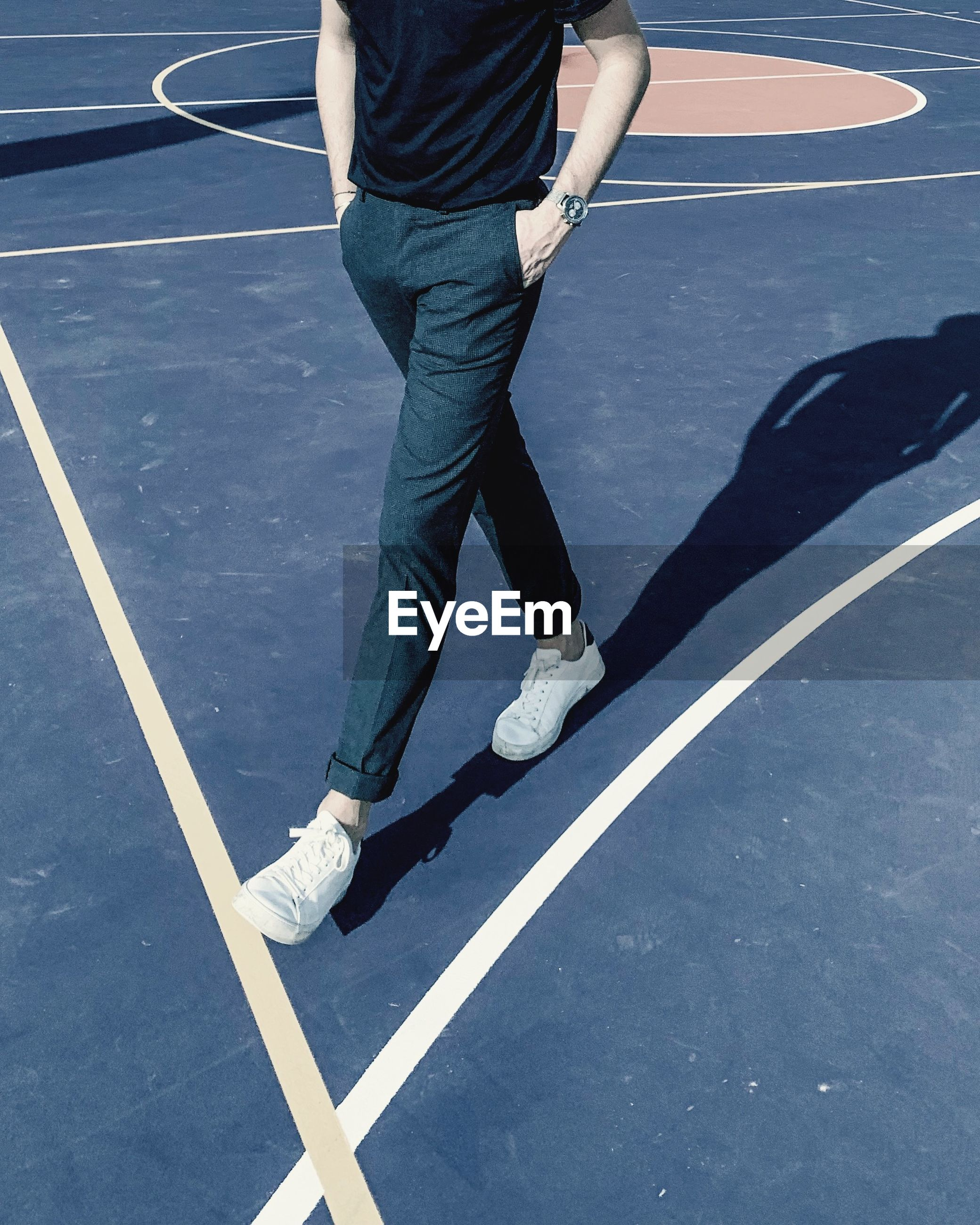 Low section of man walking on basketball court