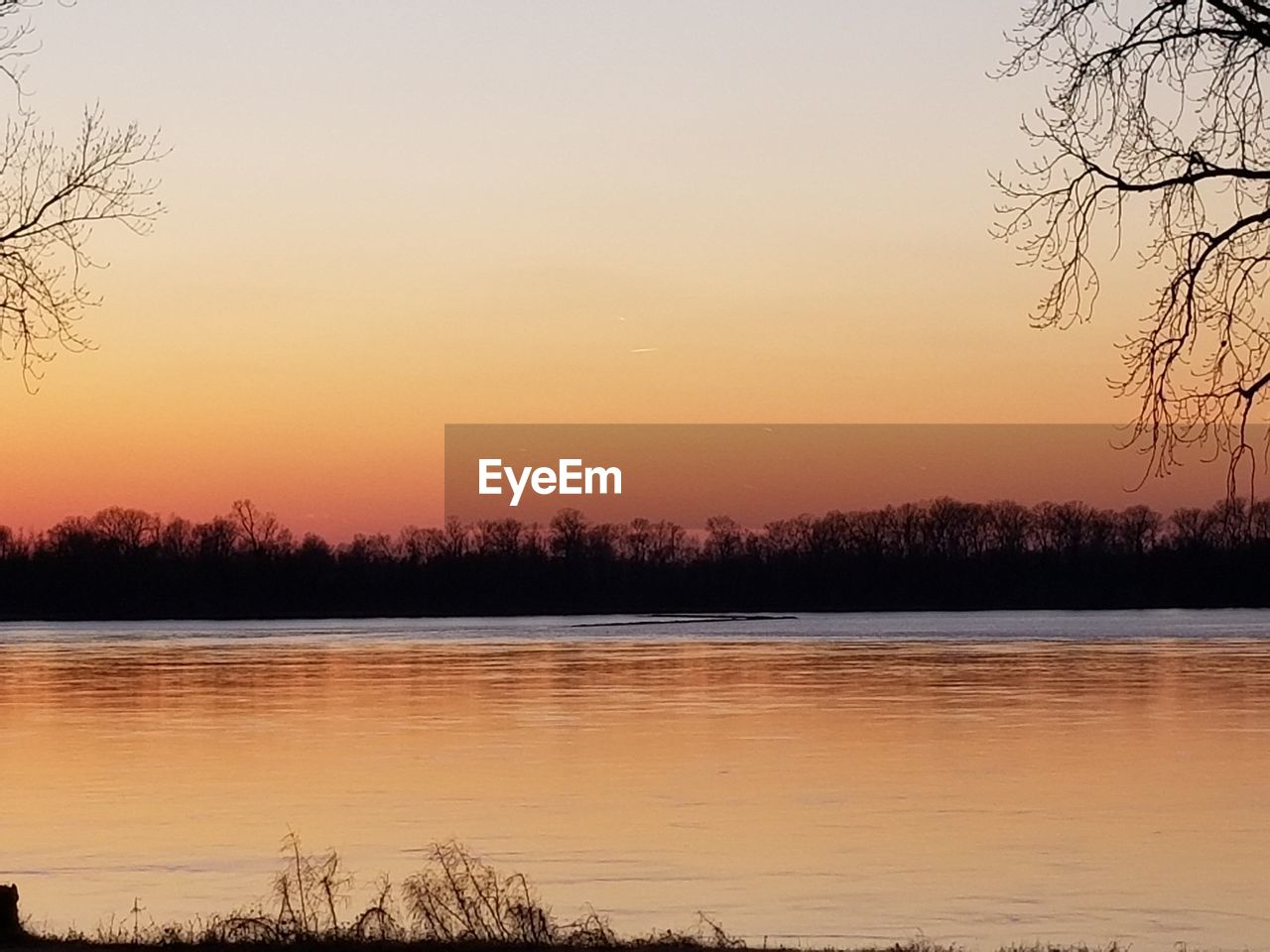 sunset, nature, beauty in nature, tree, scenics, tranquility, water, tranquil scene, lake, reflection, no people, orange color, sky, silhouette, outdoors, bare tree