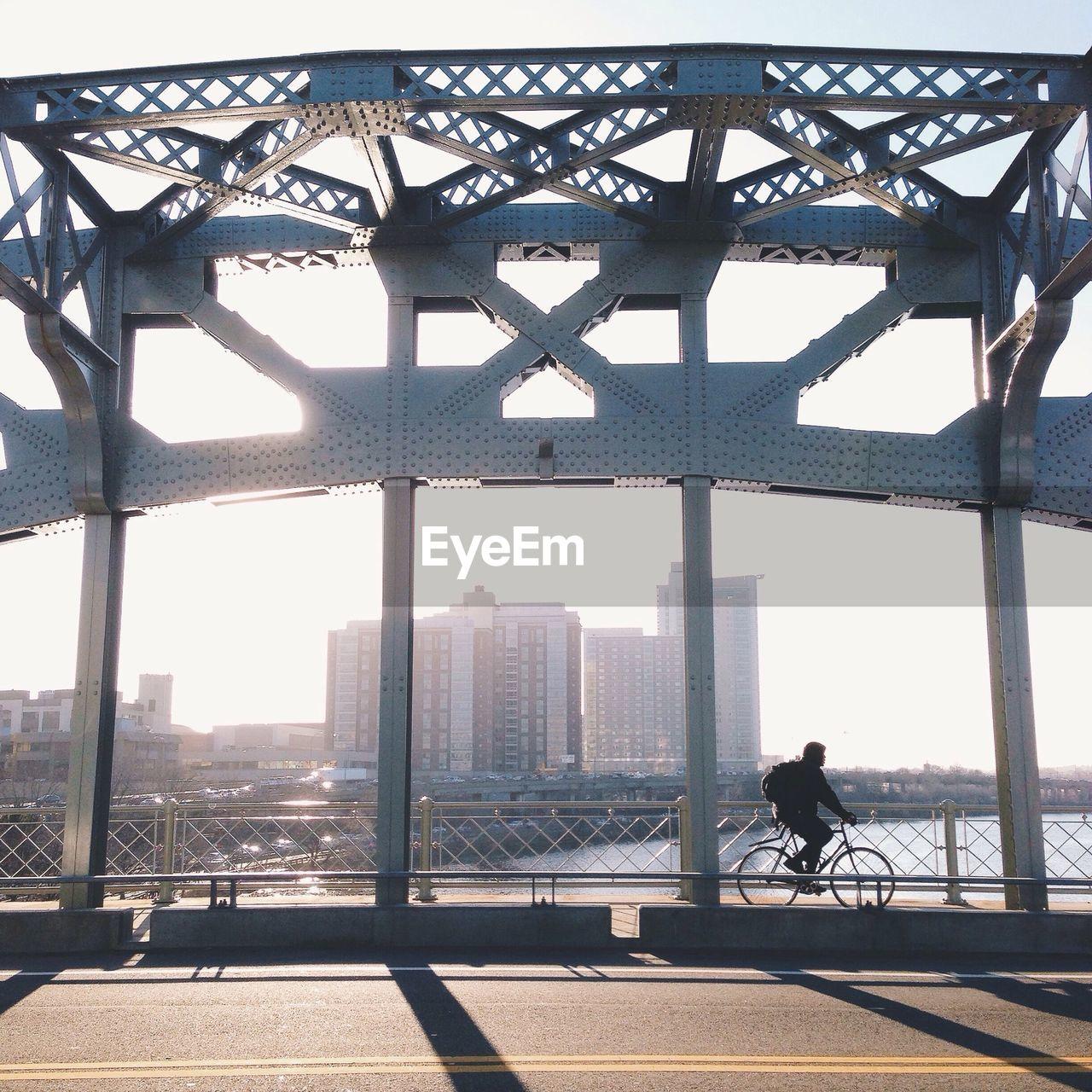 Man cycling on bridge against sky