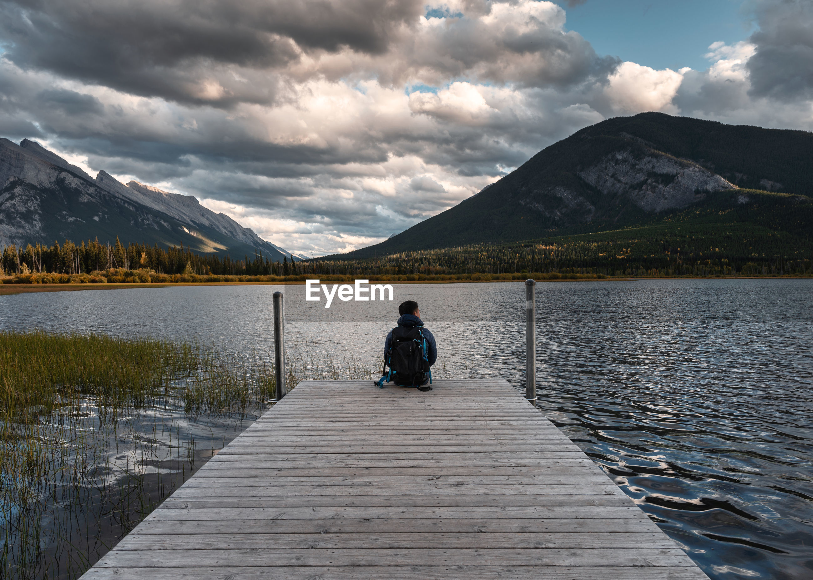 REAR VIEW OF MAN SITTING ON LAKE AGAINST MOUNTAINS