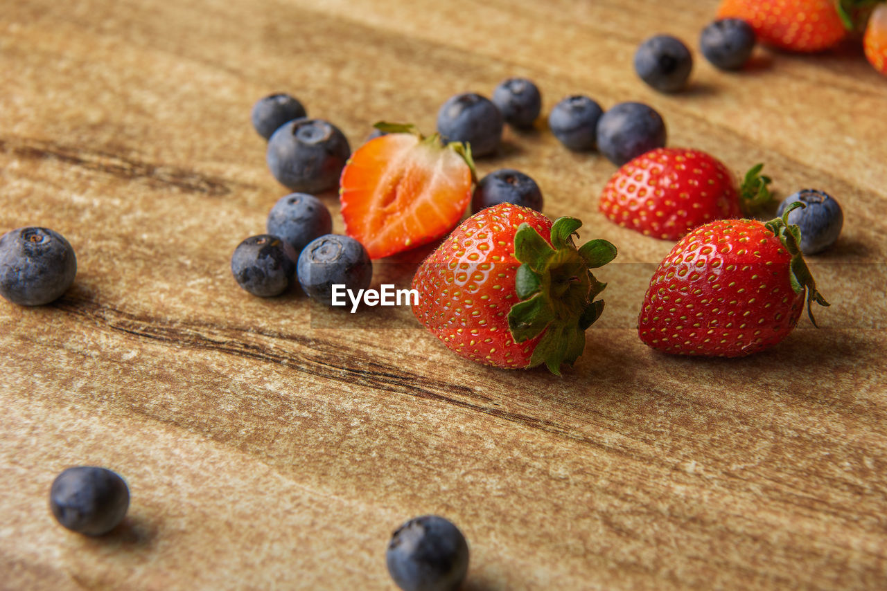 fruit, berry fruit, healthy eating, food, food and drink, freshness, blueberry, still life, wellbeing, indoors, strawberry, close-up, table, wood - material, no people, red, high angle view, selective focus, large group of objects, ripe