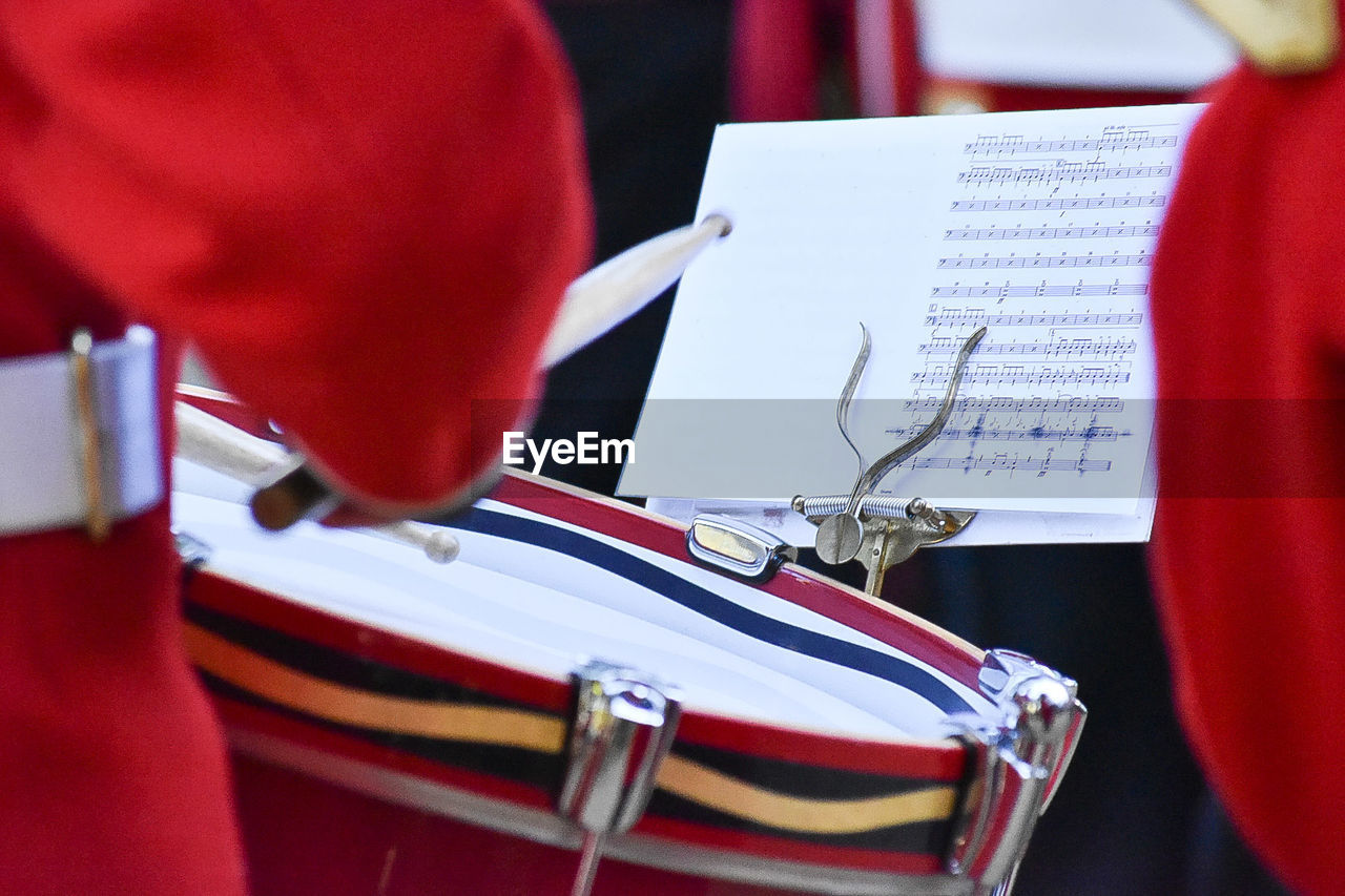 red, arts culture and entertainment, close-up, paper, sheet music, publication, indoors, sheet, music, people, book, musical instrument, selective focus, musical equipment, focus on foreground, real people, day, patriotism, marching band