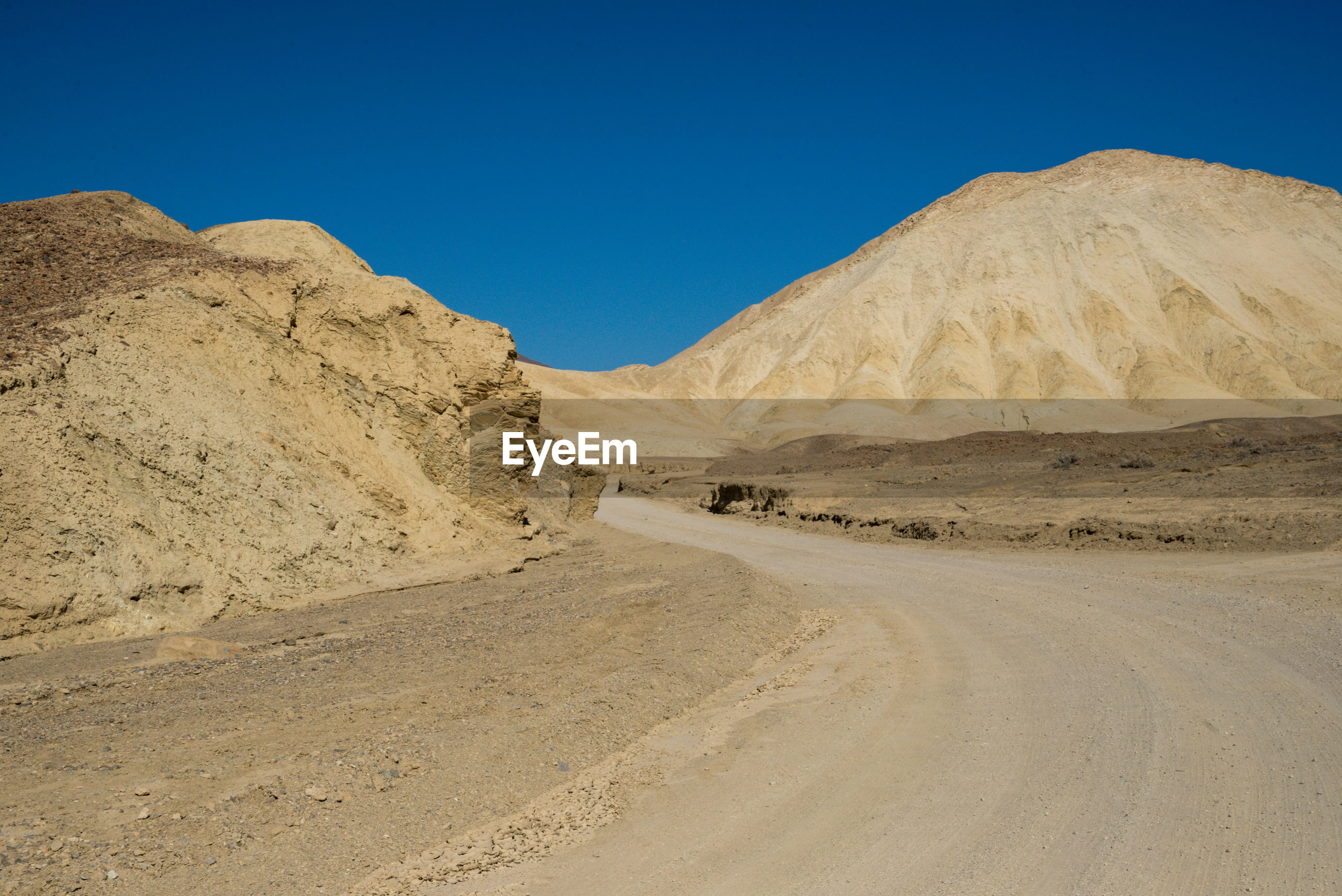 Road in desert against clear blue sky