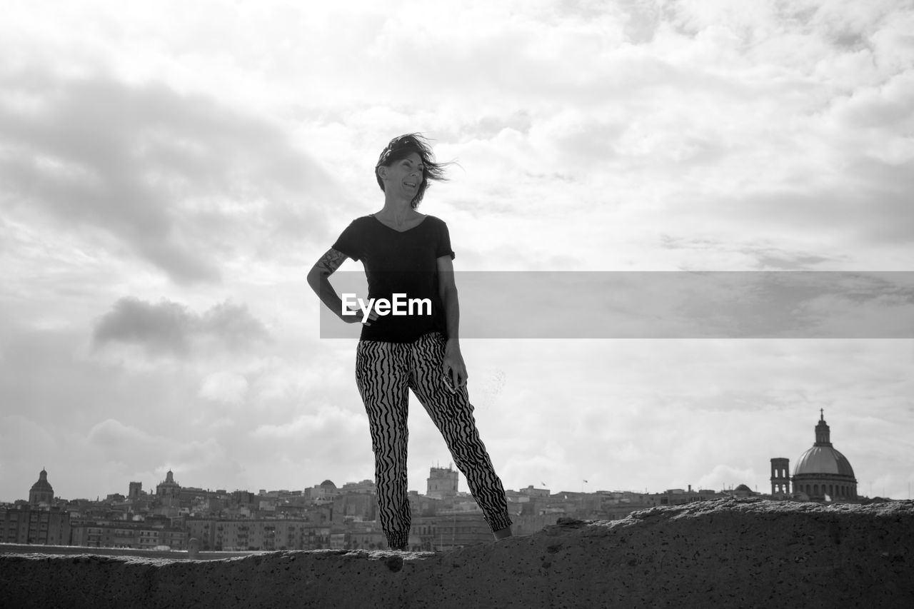 cloud - sky, sky, one person, real people, standing, lifestyles, full length, nature, women, day, leisure activity, young adult, females, architecture, built structure, land, young women, casual clothing, outdoors