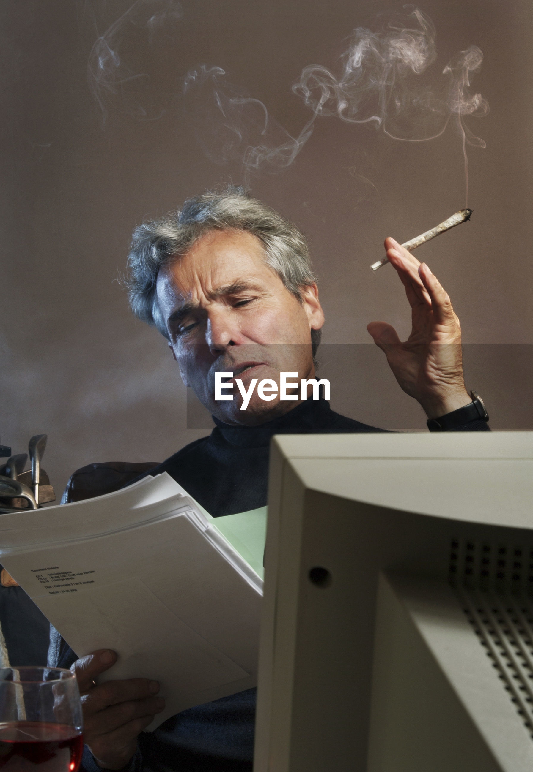Senior man holding cigarette while working in office
