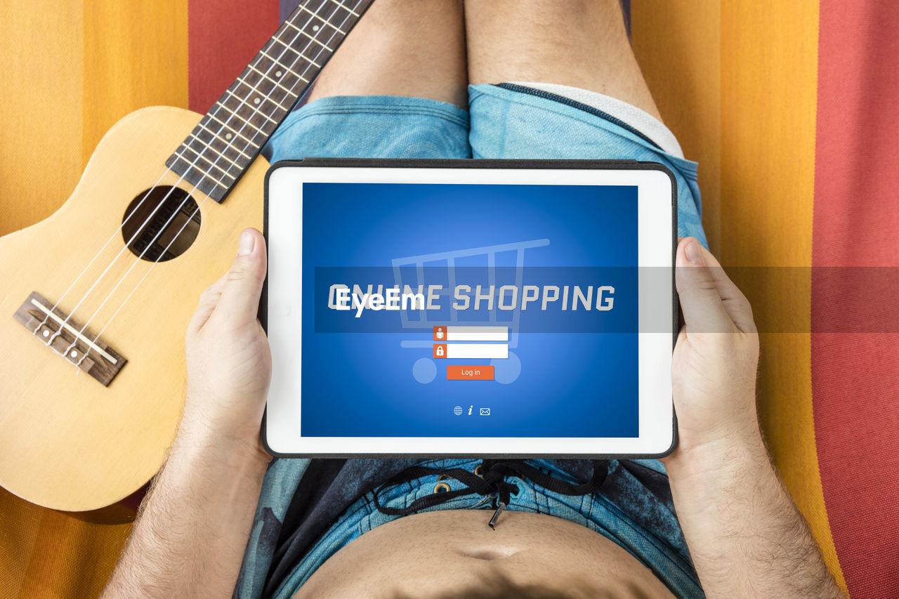 Midsection of man using digital tablet while sitting on bed by guitar at home