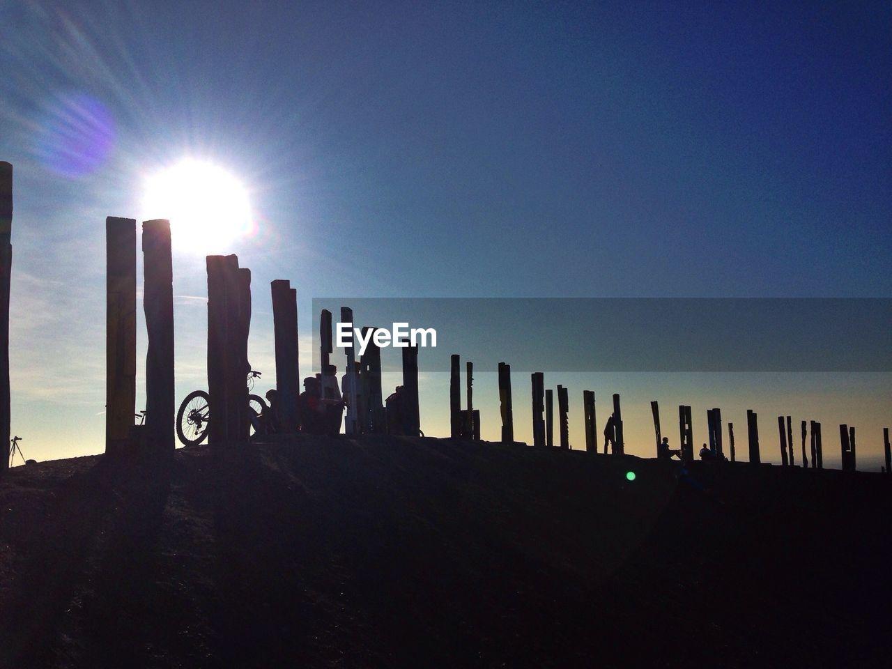 Silhouette pier against clear blue sky