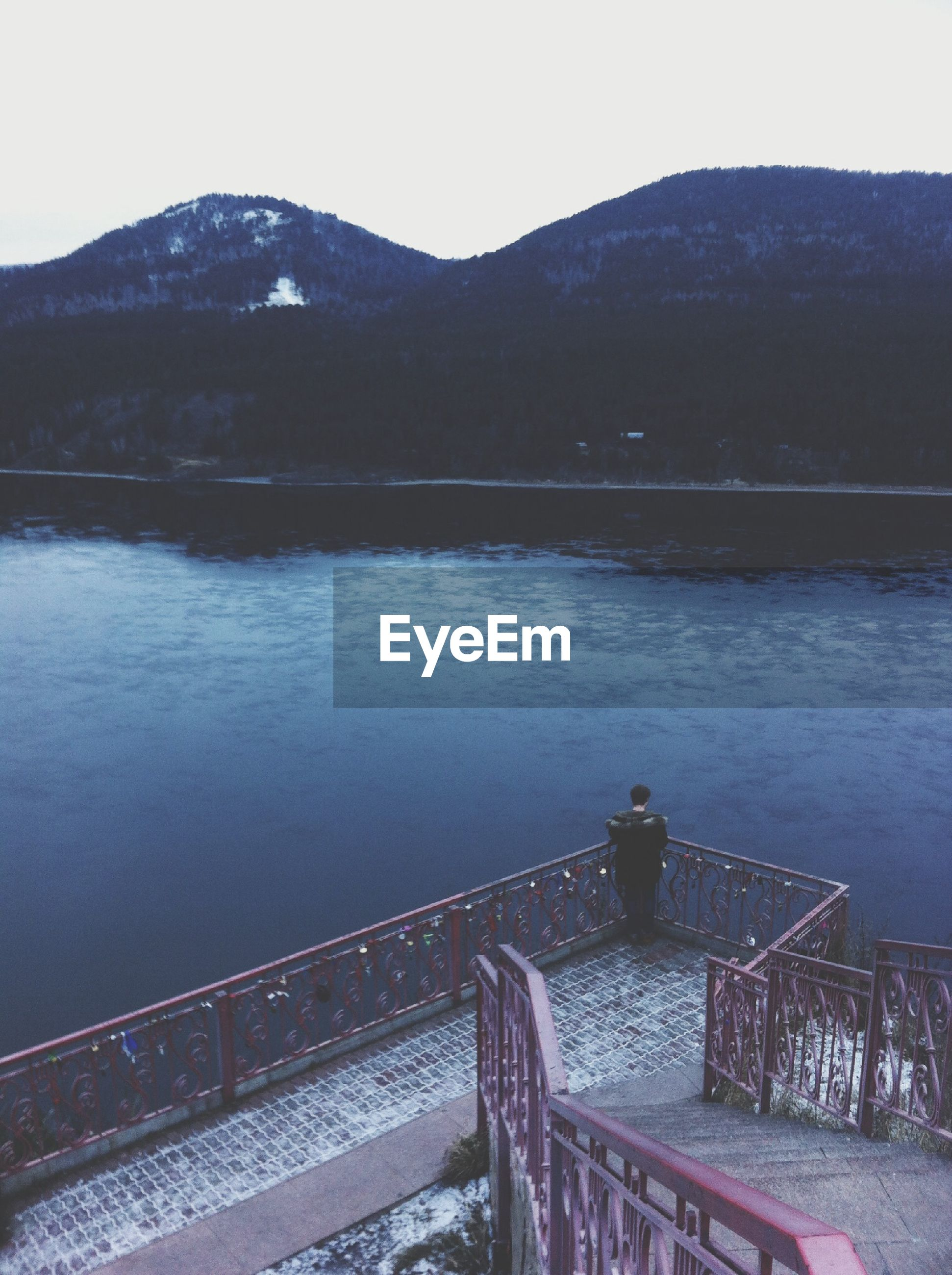 mountain, water, mountain range, river, lake, built structure, railing, architecture, tranquility, bridge - man made structure, scenics, clear sky, tranquil scene, sky, nature, beauty in nature, connection, outdoors, sea, building exterior