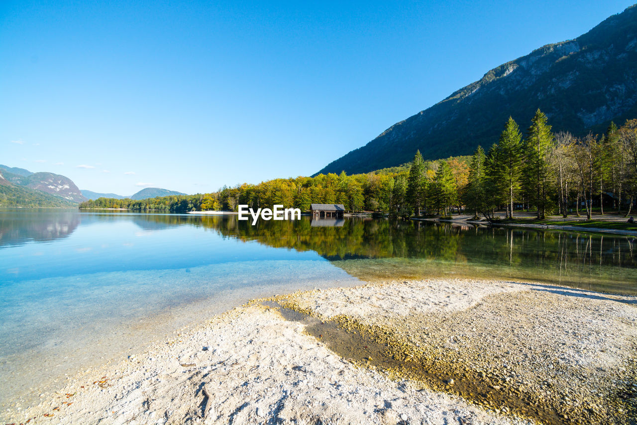 water, sky, mountain, beauty in nature, scenics - nature, lake, tranquility, tranquil scene, plant, nature, tree, reflection, no people, blue, day, clear sky, copy space, idyllic, non-urban scene, outdoors