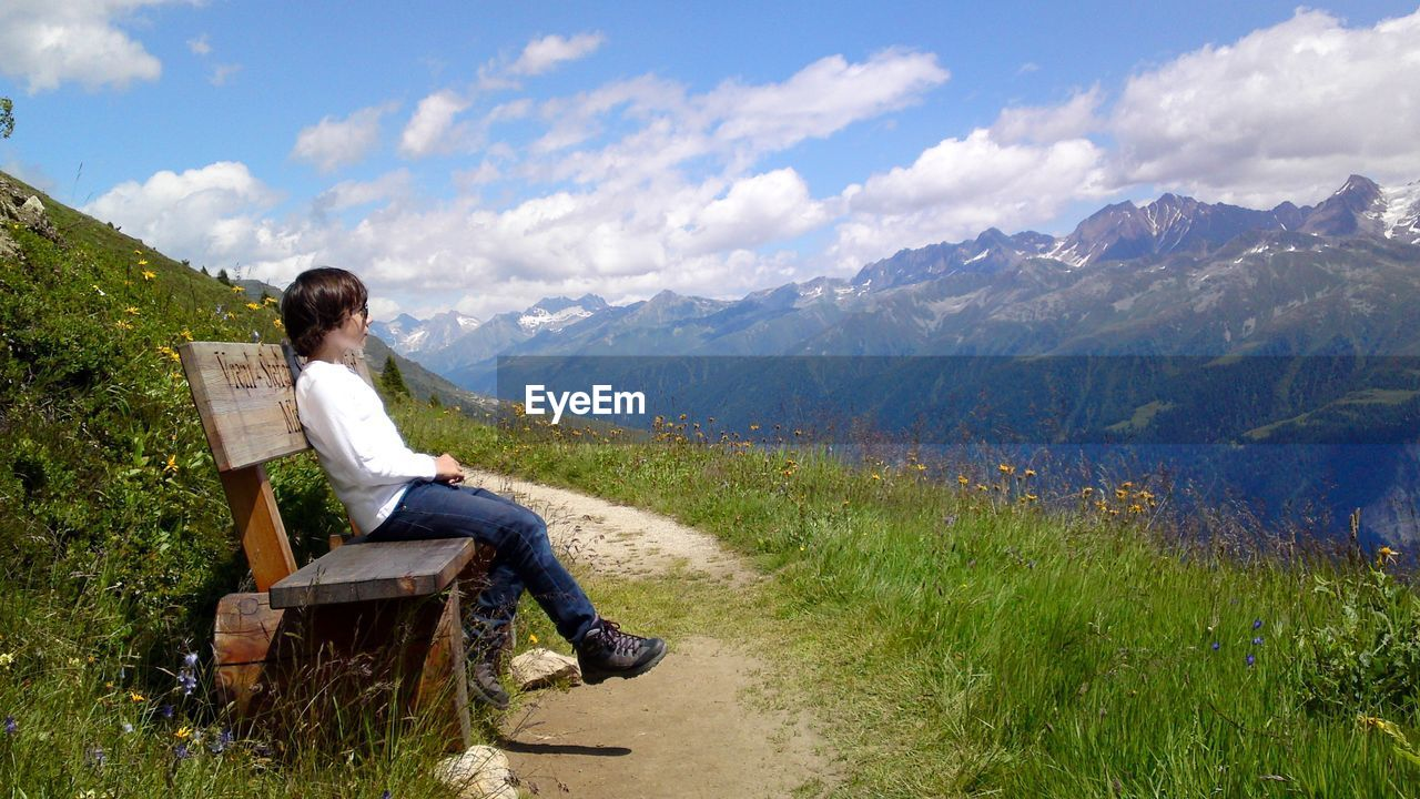 Full Length Side View Of Boy Sitting On Wooden Bench At Mountain