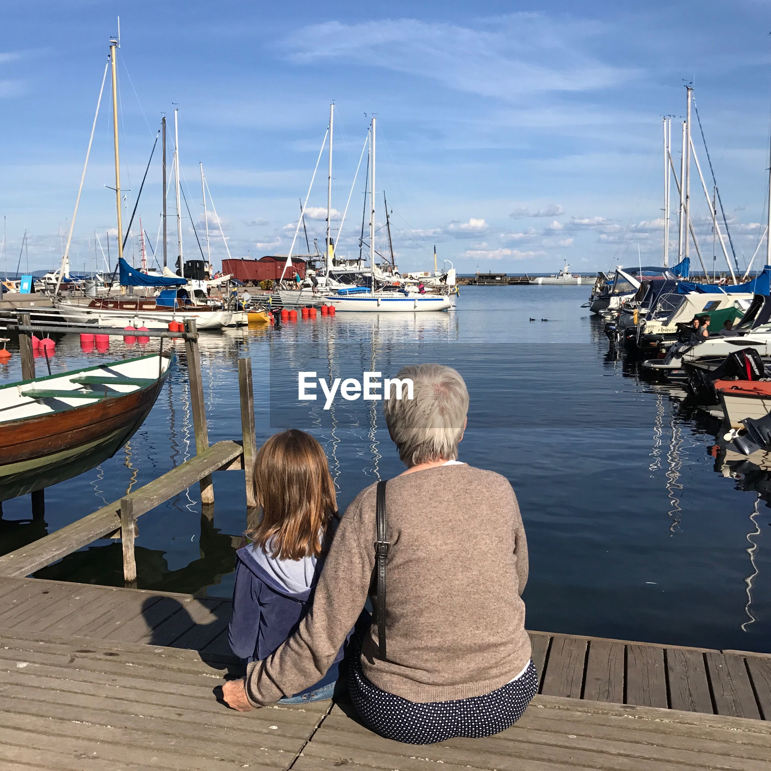 Rear view of grandmother and granddaughter sitting on pier at harbor