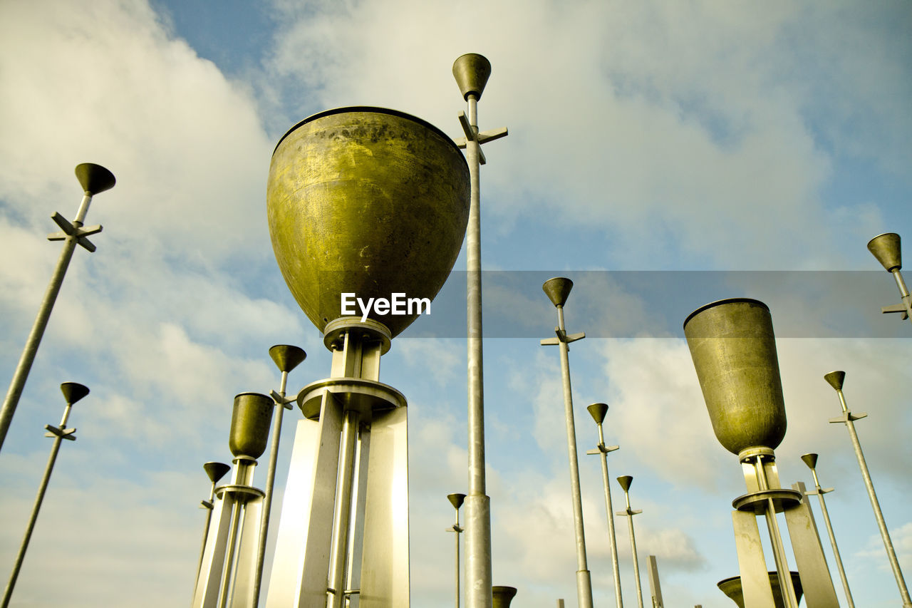 sky, low angle view, cloud - sky, street light, no people, street, metal, nature, day, lighting equipment, outdoors, gold colored, focus on foreground, green color, retro styled, built structure, antique, equipment, pole