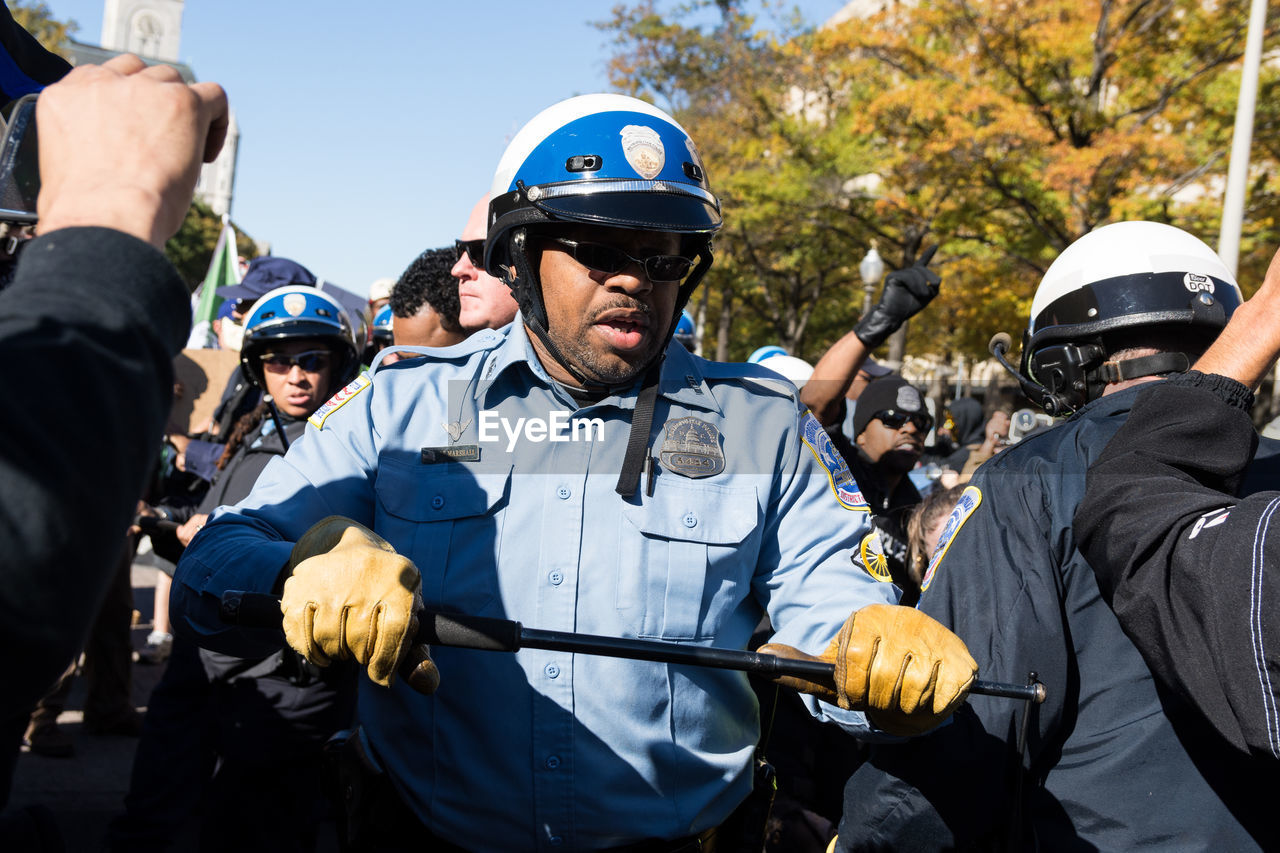 police force, helmet, uniform, real people, police uniform, headwear, day, outdoors, men, law, military uniform, weapon, justice - concept, riot, people