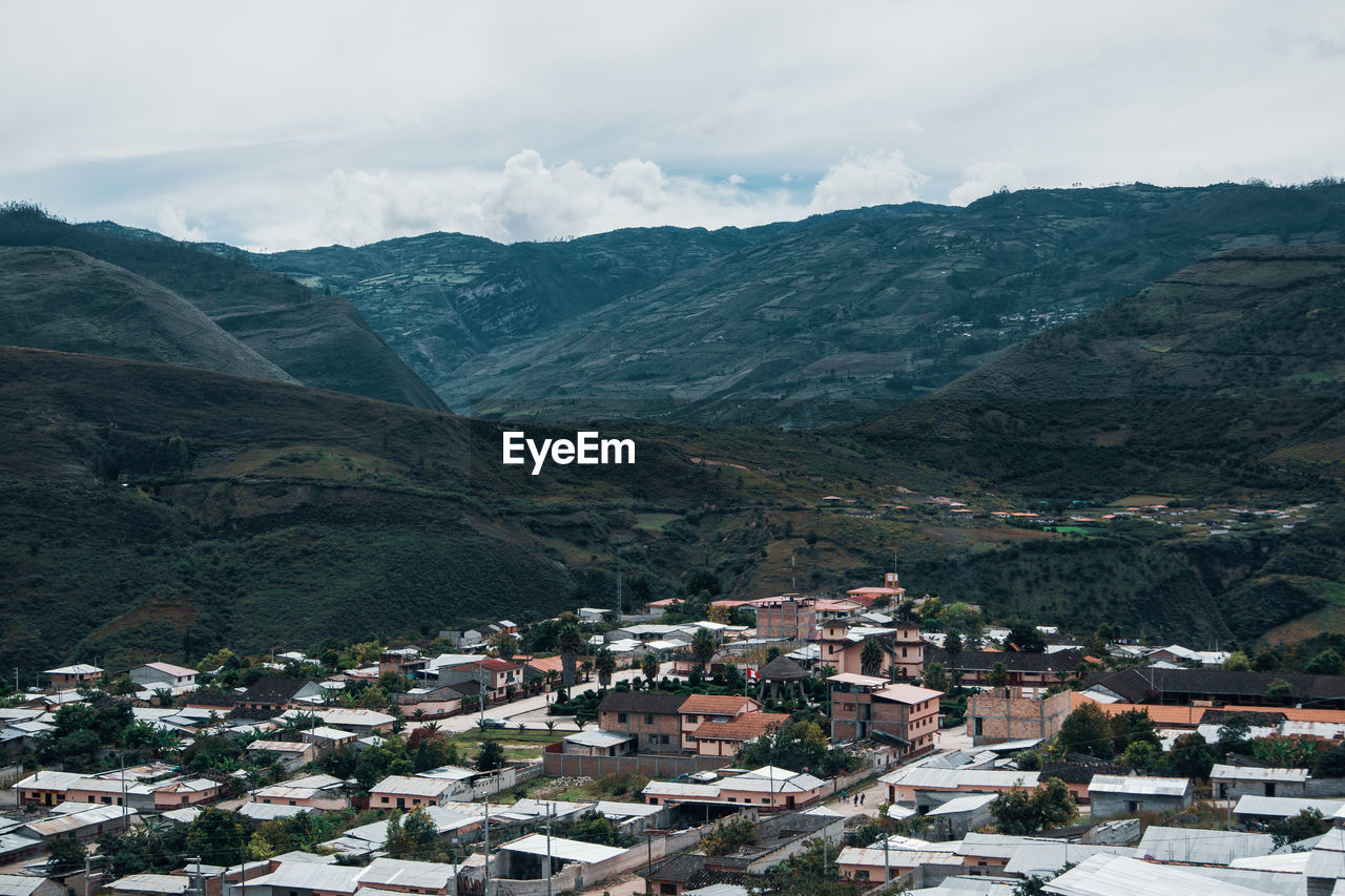 mountain, architecture, building exterior, built structure, building, mountain range, residential district, sky, city, scenics - nature, environment, landscape, beauty in nature, house, nature, town, day, cloud - sky, no people, high angle view, outdoors, community, townscape, cityscape, range