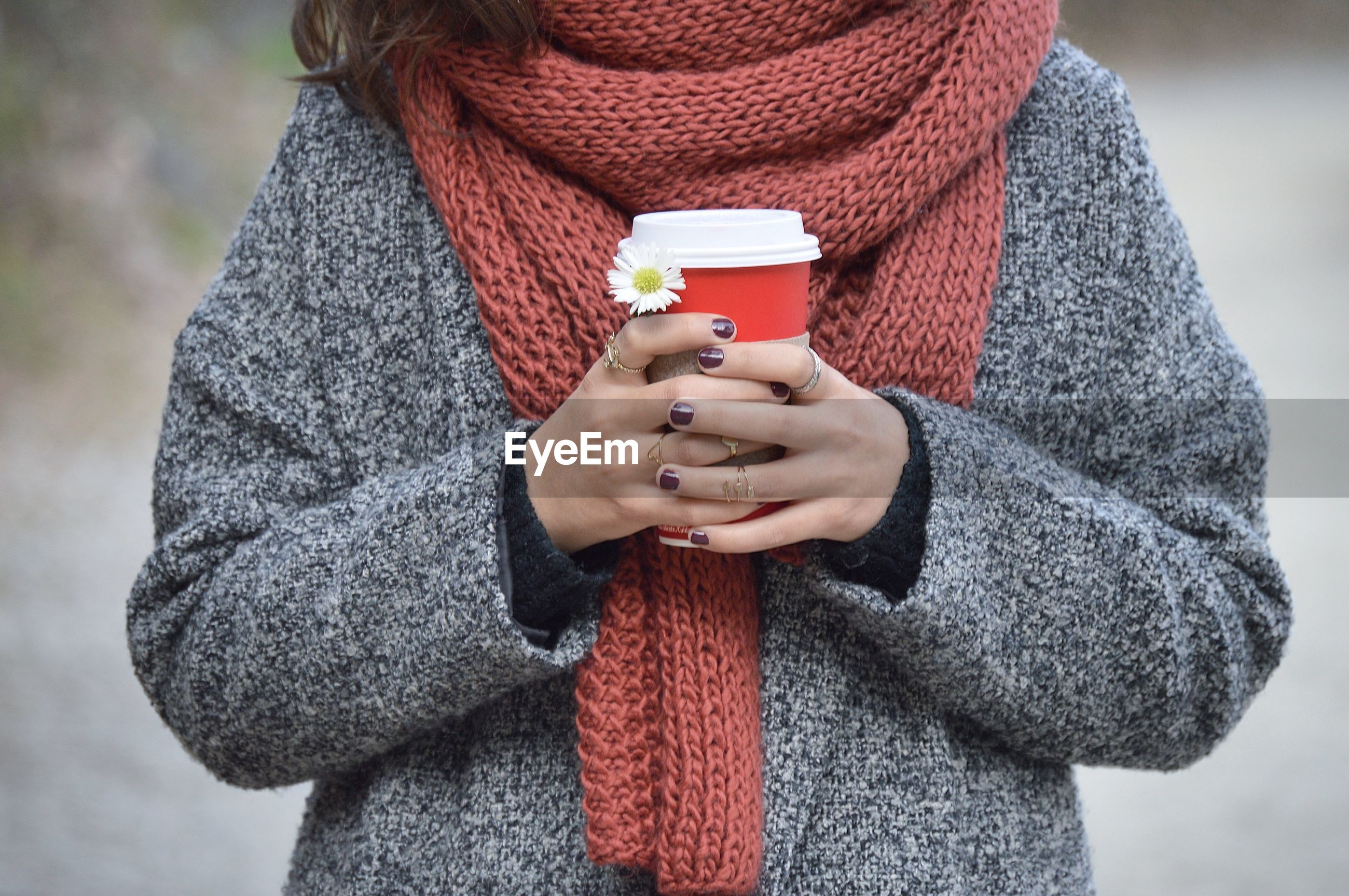 one person, real people, holding, sweater, cold temperature, winter, warm clothing, midsection, front view, scarf, focus on foreground, leisure activity, casual clothing, red, outdoors, day, close-up, drink, lifestyles, standing, young adult, human hand, people