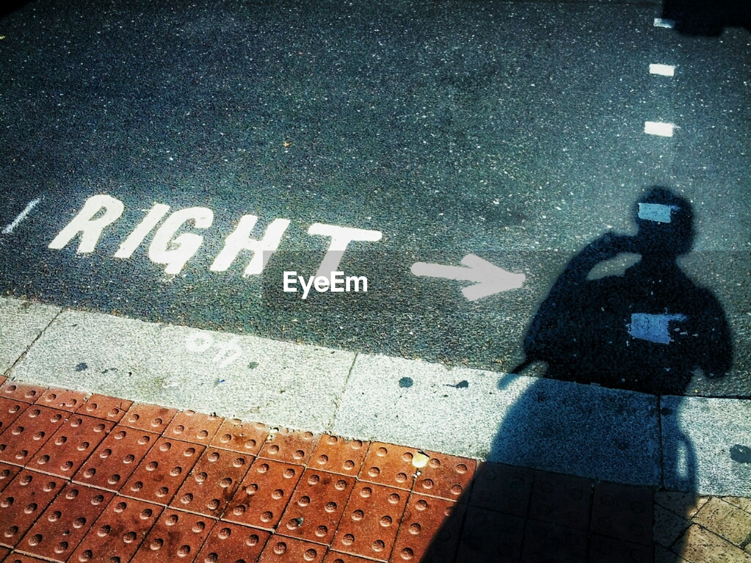Close-up of right word and arrow sign on road