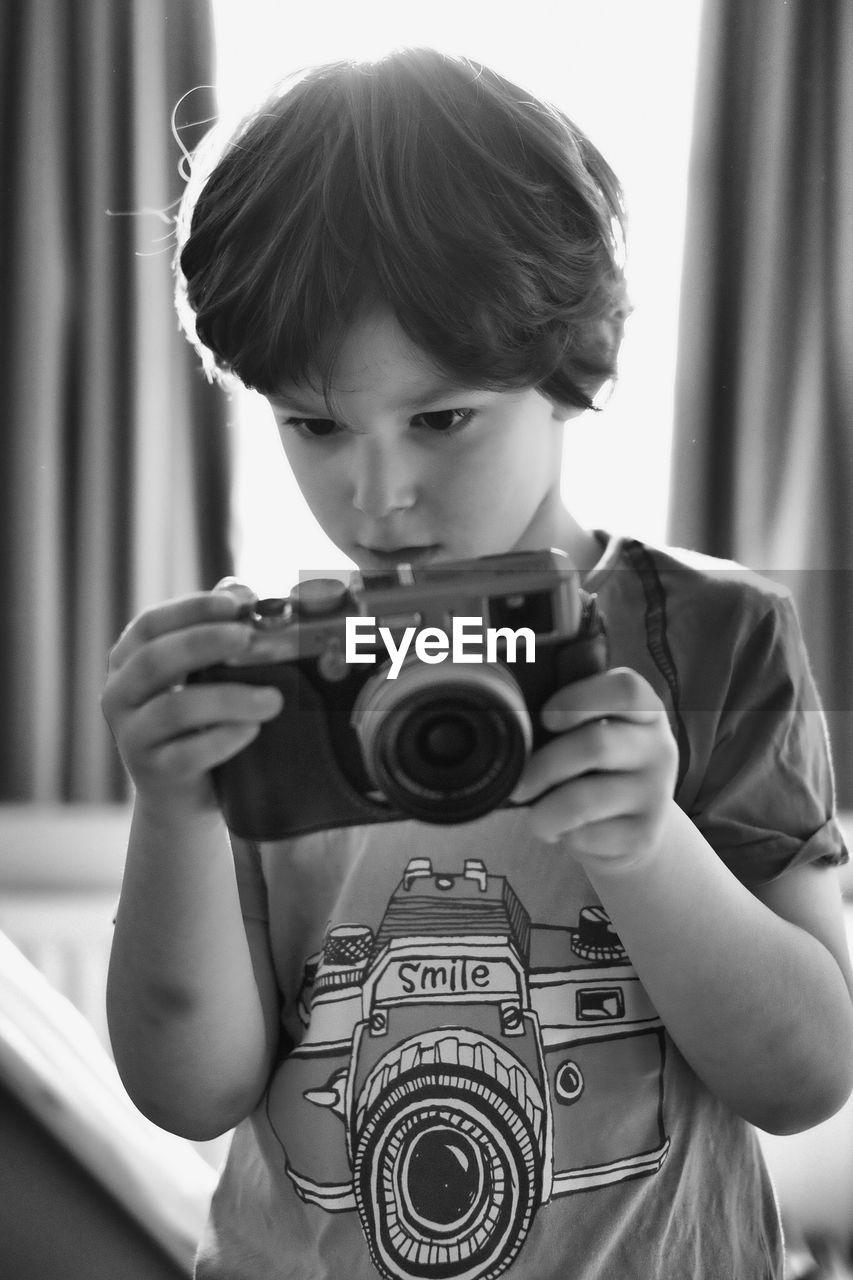 Boy using camera at home