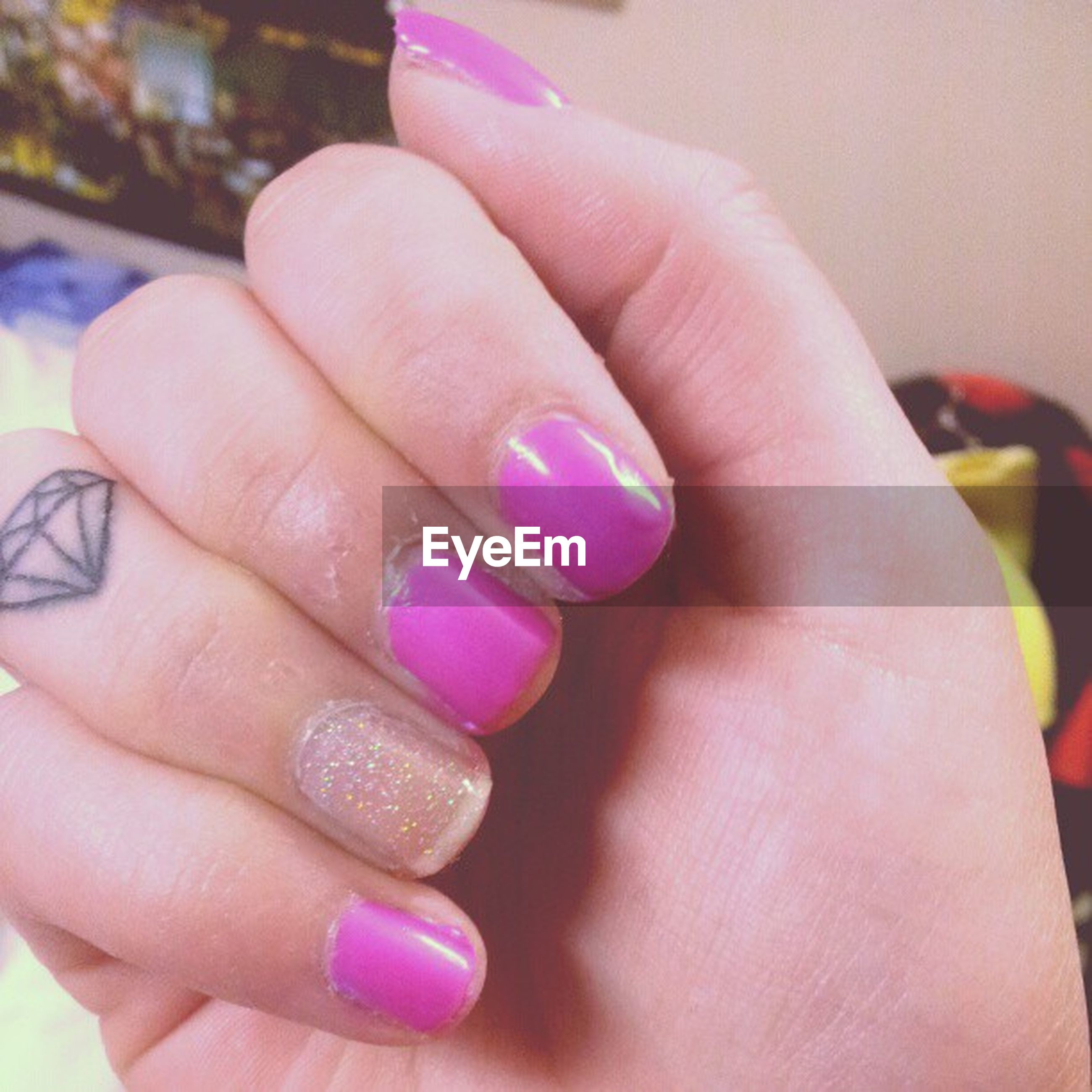 person, part of, human finger, close-up, cropped, holding, indoors, multi colored, unrecognizable person, focus on foreground, nail polish, showing, jewelry, selective focus, pink color, high angle view, ring