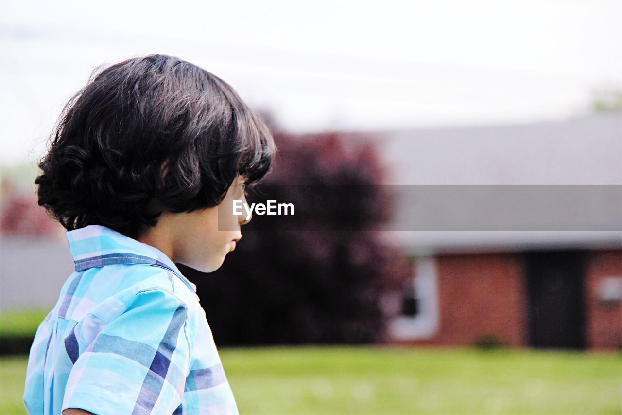 Side view of boy looking away while standing against sky at yard