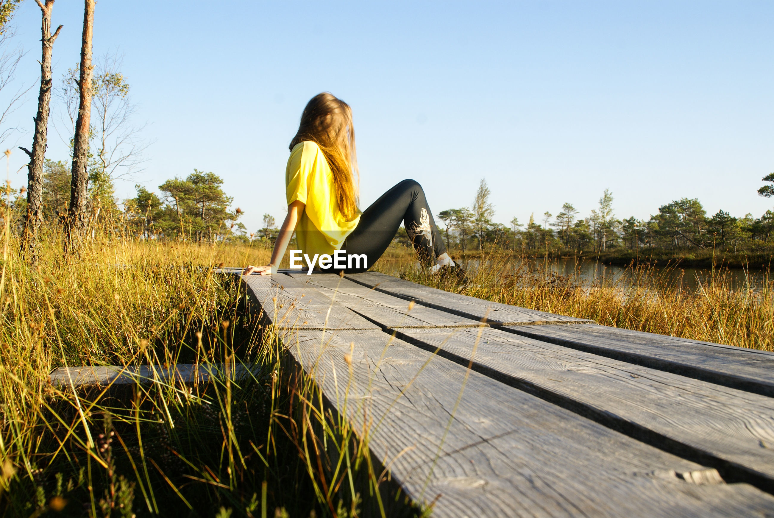 Young woman sitting on boardwalk against clear sky
