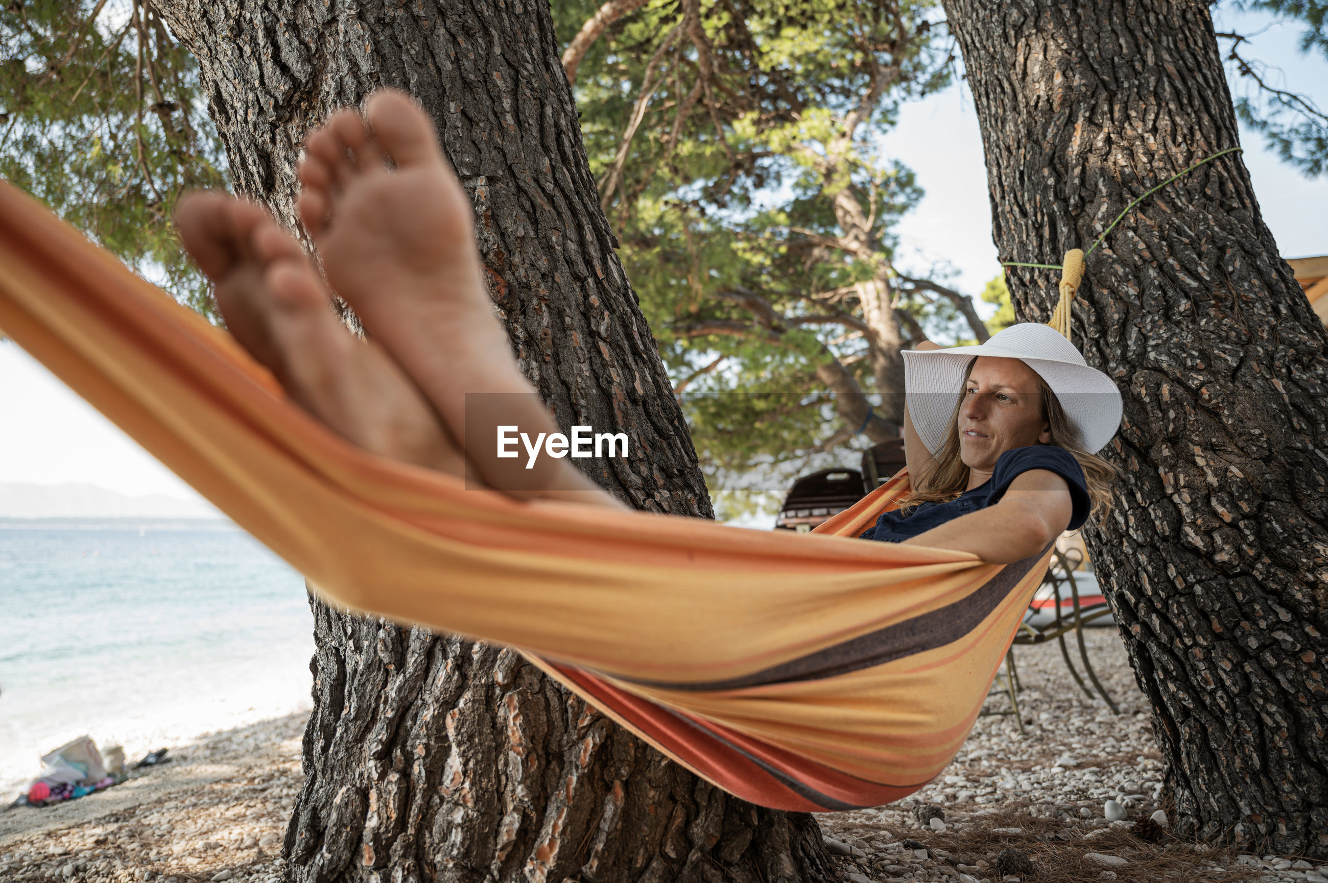 YOUNG WOMAN RELAXING ON HAMMOCK BY TREE TRUNK