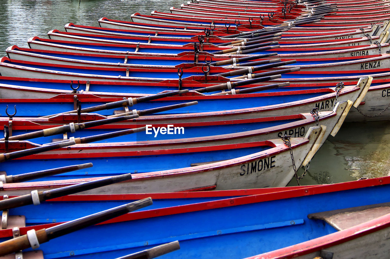 HIGH ANGLE VIEW OF MULTI COLORED BOATS MOORED IN ROW