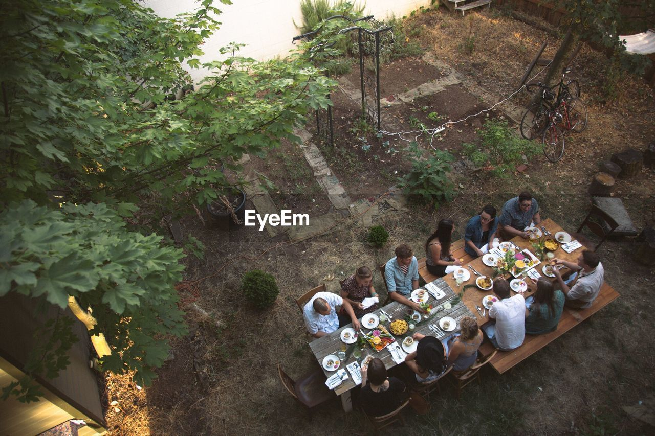 High Angle View Of People Having Food At Table In Yard