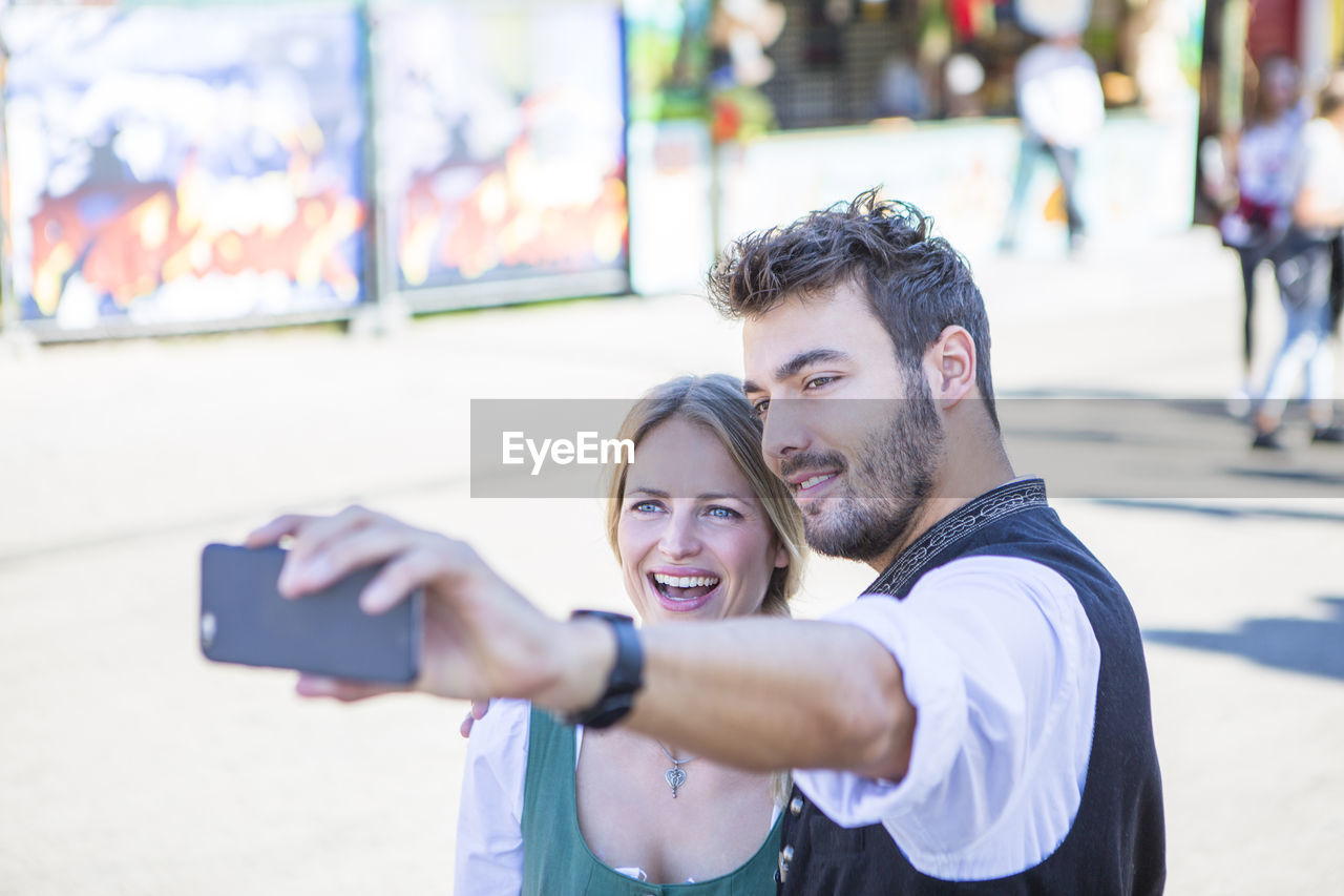 Smiling Man And Woman Taking Selfie While Standing On Street At Event