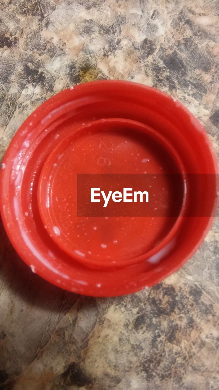 red, high angle view, directly above, no people, indoors, still life, close-up, food and drink, table, container, drink, marble, wood - material, bowl, empty, lid, food, flooring, wax, textile