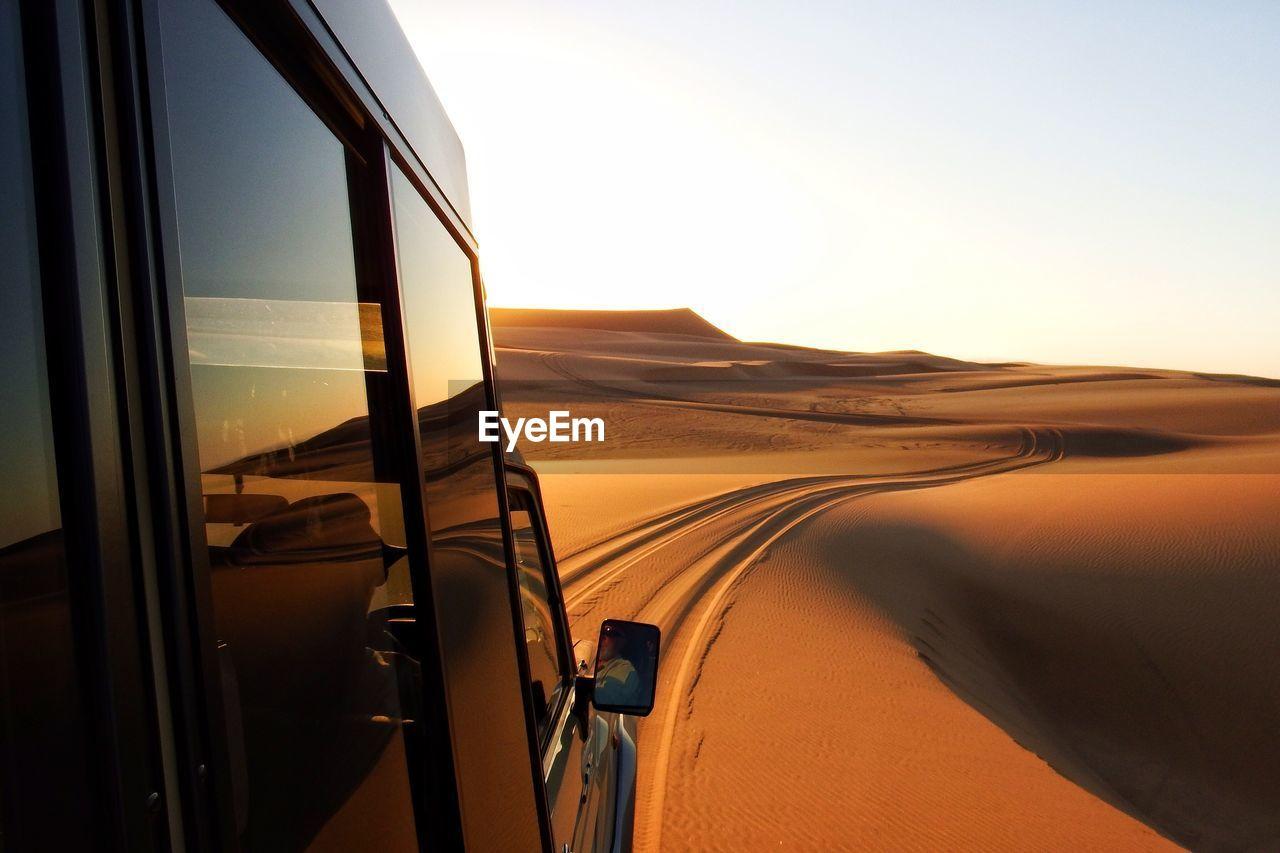 Off-Road Vehicle On Sand Dunes Of Namib Desert Against Sky