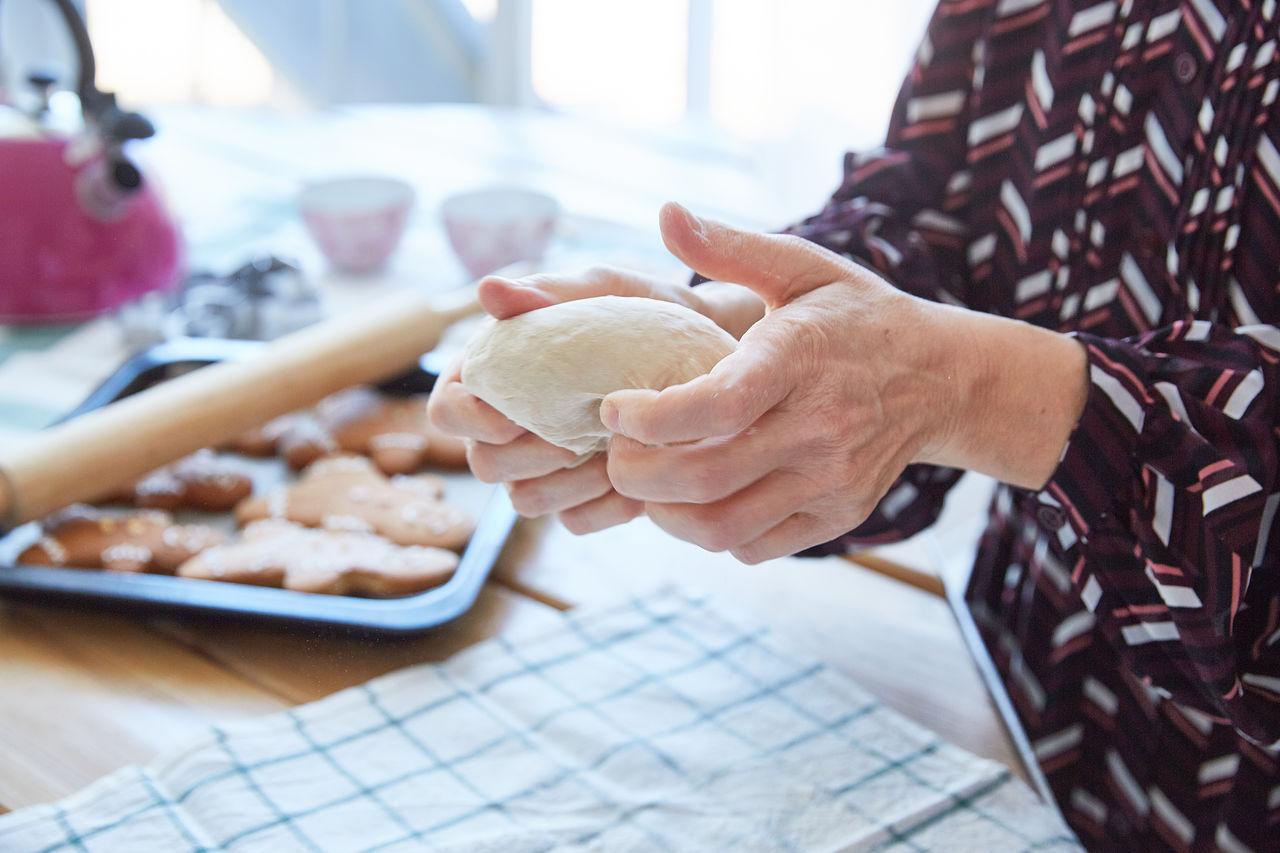 Female hands of an elderly woman knead the dough. grandma makes cookies. light background. faceless.