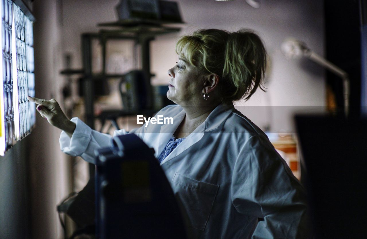 Side View Of Female Doctor Looking At Medical X-Ray