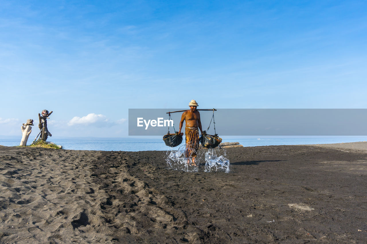 sky, water, sea, land, beach, real people, beauty in nature, scenics - nature, blue, nature, sand, men, day, lifestyles, horizon, non-urban scene, horizon over water, people, occupation, outdoors, salt flat