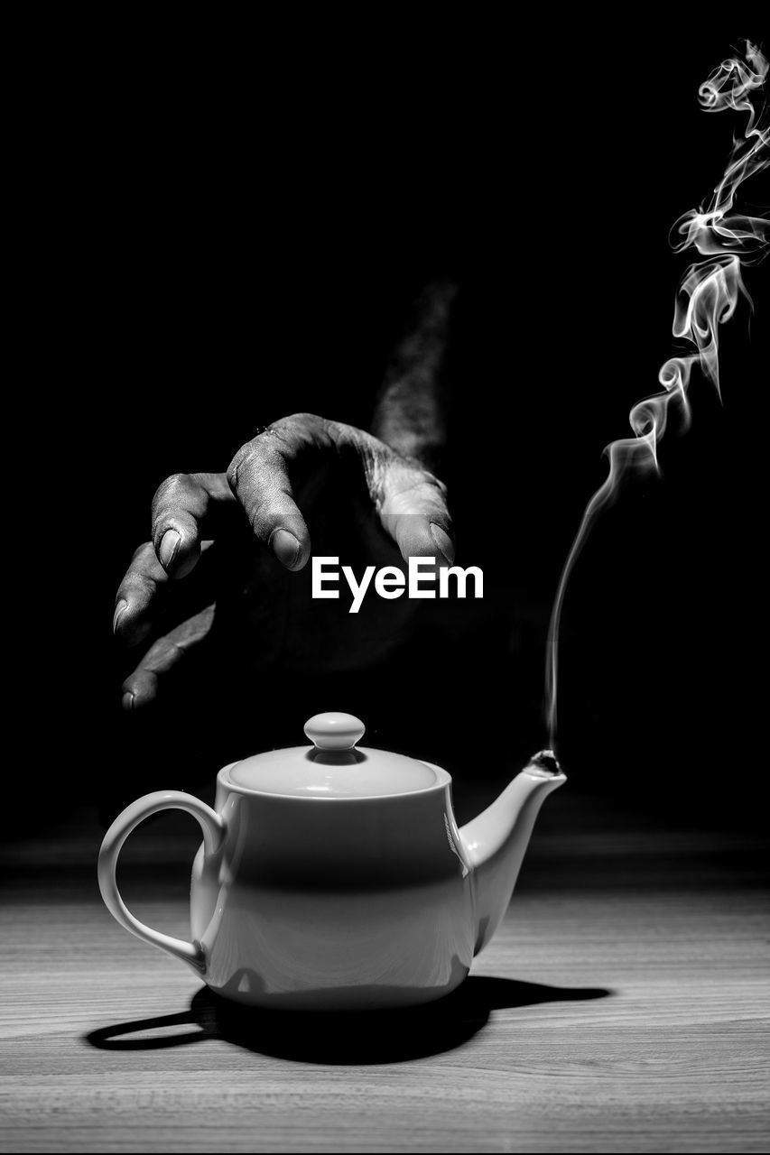Cropped hand of person over teapot on table