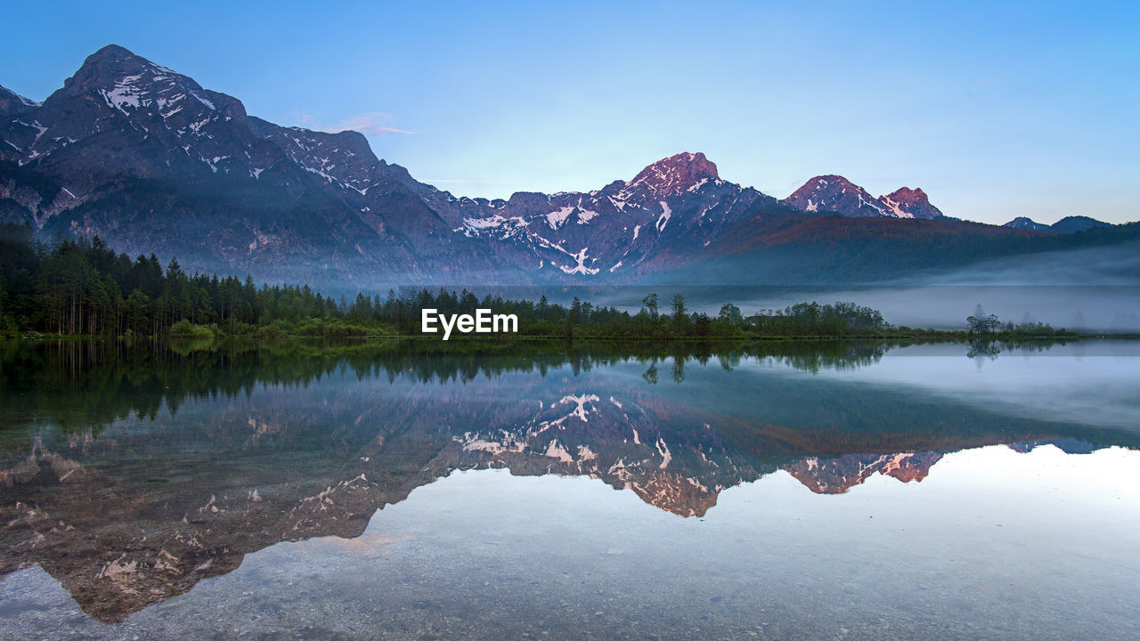 reflection, water, scenics - nature, mountain, lake, tranquil scene, tranquility, beauty in nature, sky, mountain range, non-urban scene, waterfront, idyllic, nature, symmetry, tree, no people, day, plant, snowcapped mountain