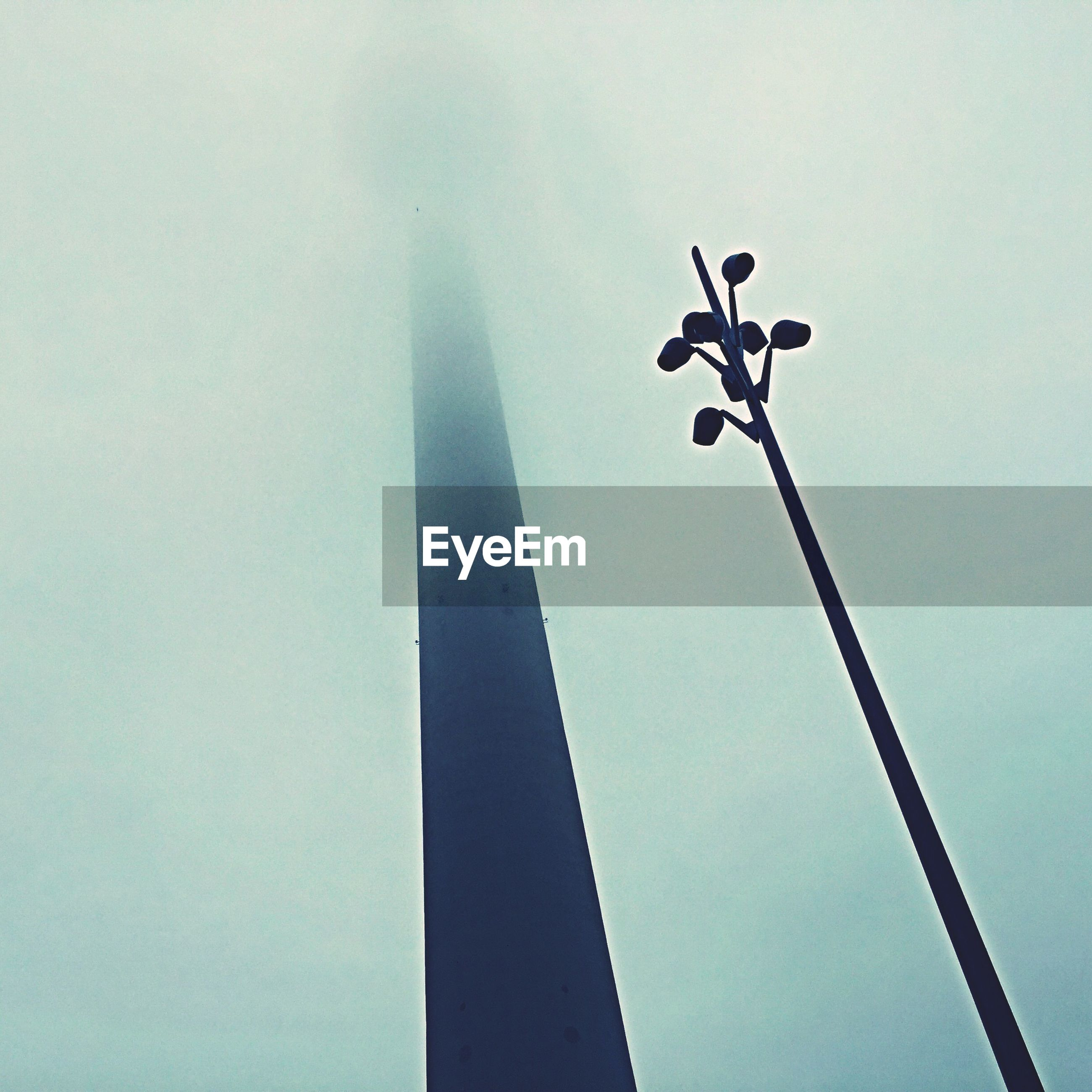 Low angle view of street light by fernsehturm during foggy weather