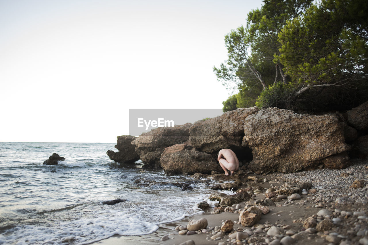 Naked man by rock formation on beach
