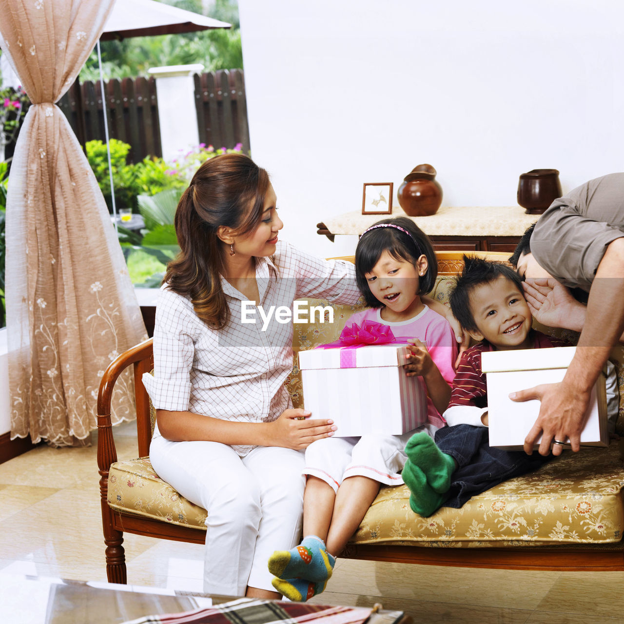 Parents giving christmas presents to children at home