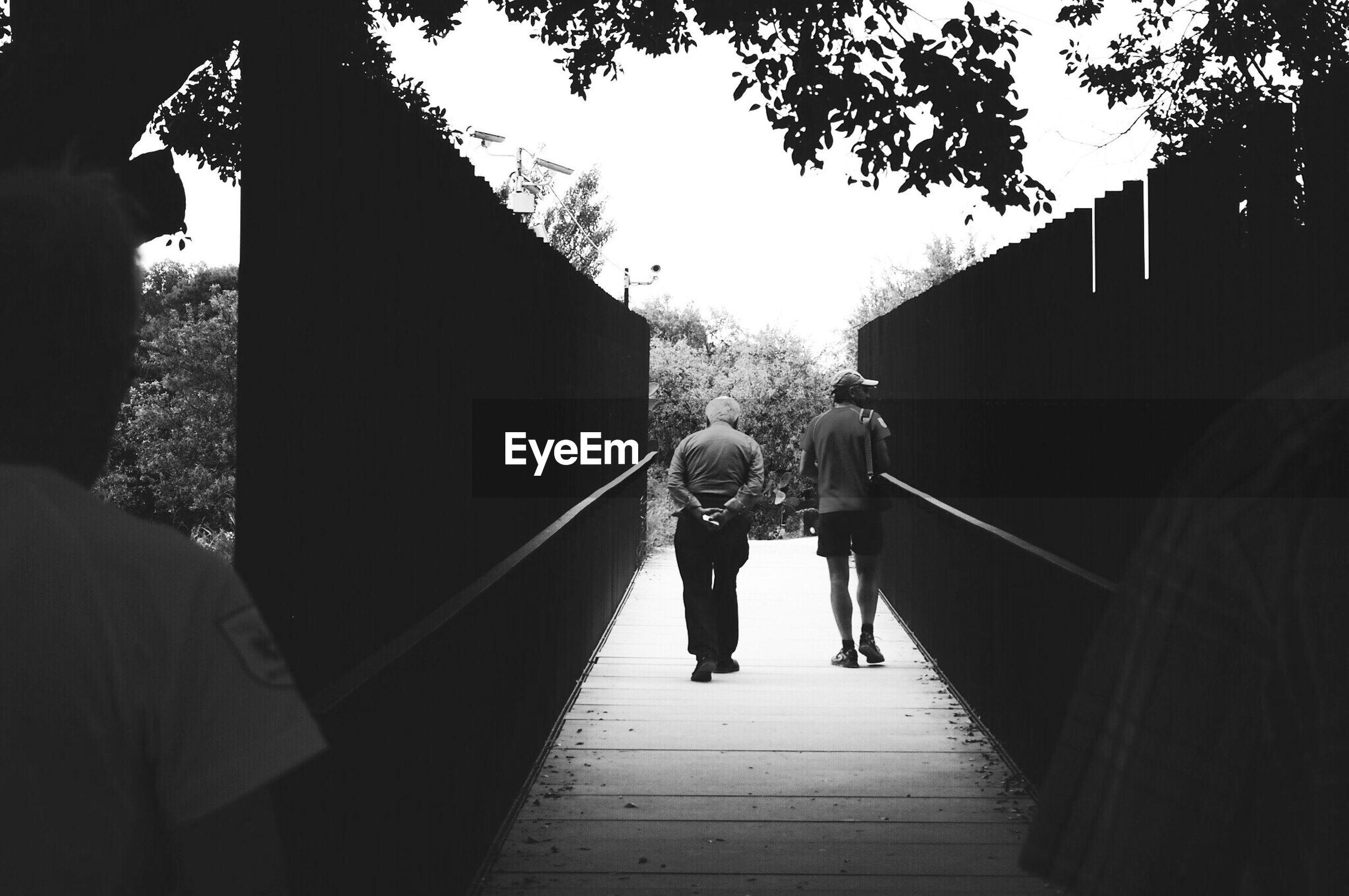 People walking on footbridge amidst fence against sky