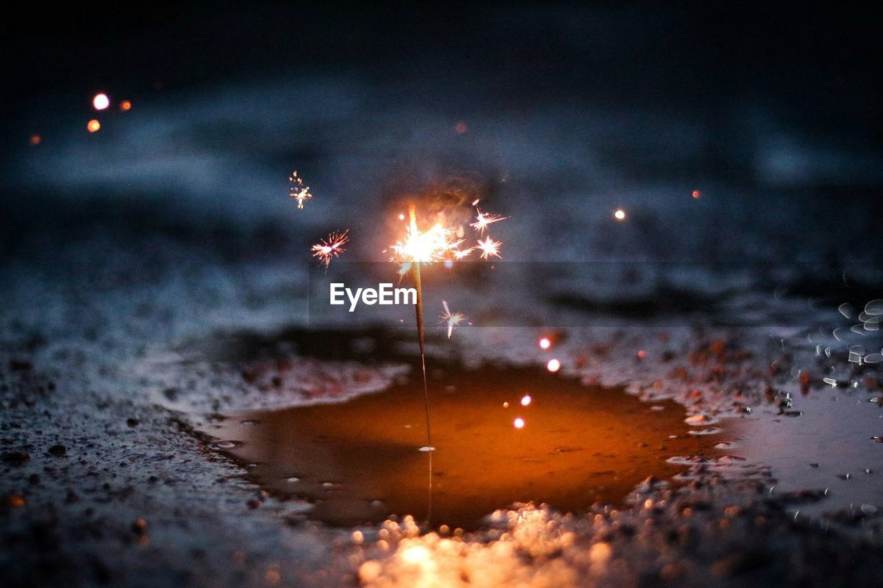 Close-Up Of Lit Sparkler In Puddle At Night